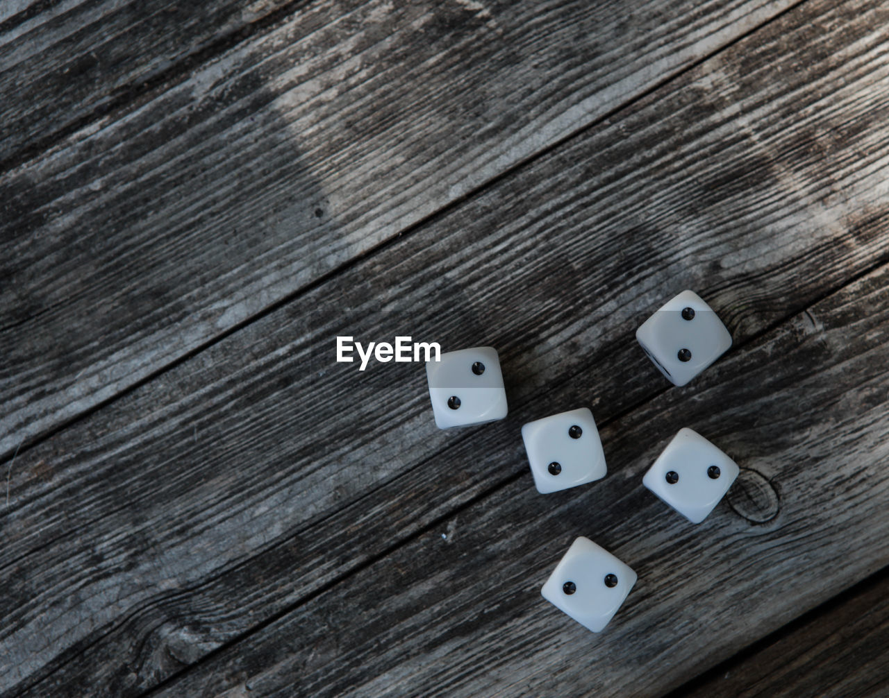wood - material, table, indoors, still life, dice, high angle view, no people, arts culture and entertainment, opportunity, leisure games, luck, gambling, group of objects, close-up, pattern, textured, shape, directly above, cube shape, leisure activity