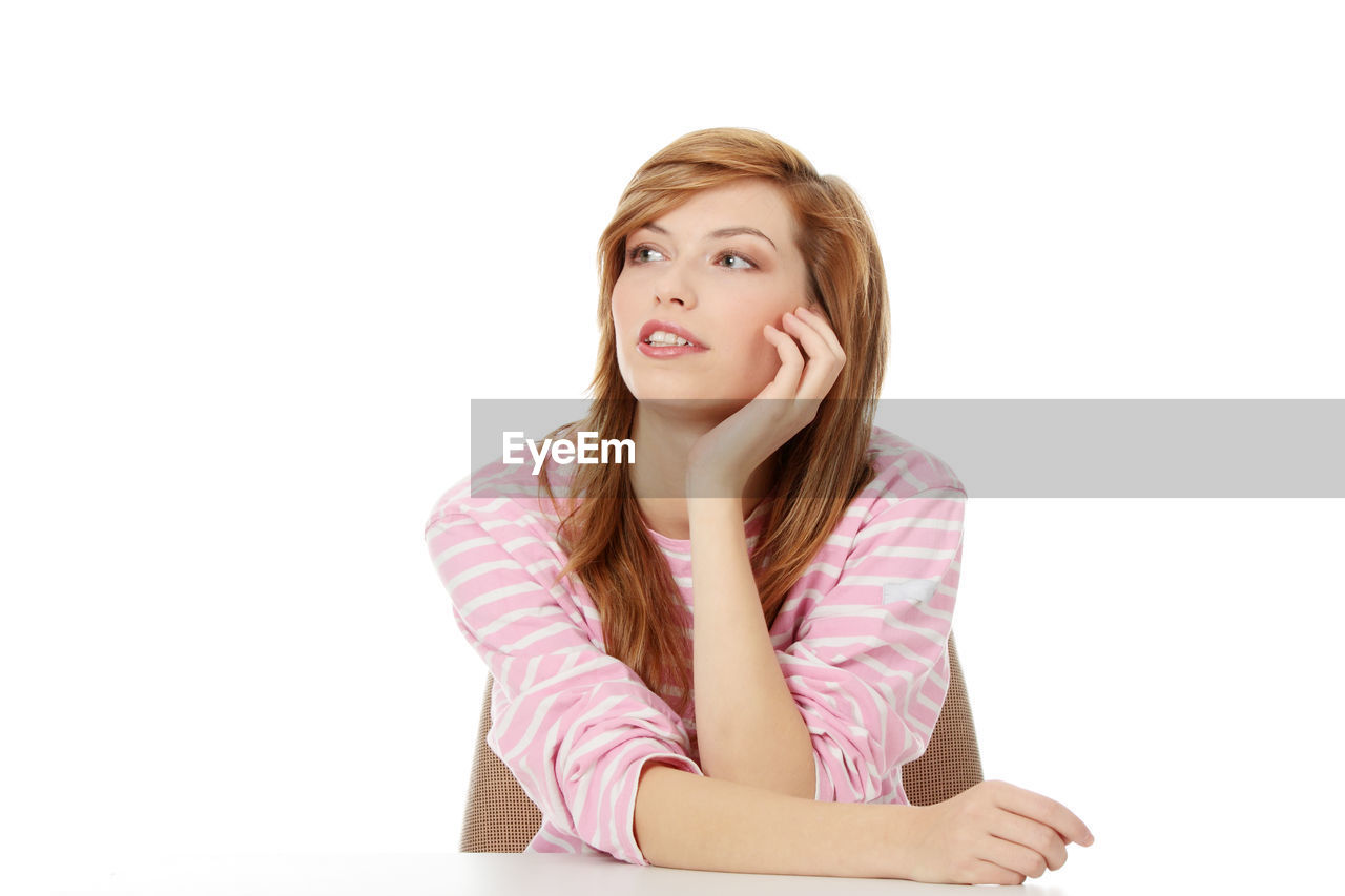 Beautiful young woman looking away against white background