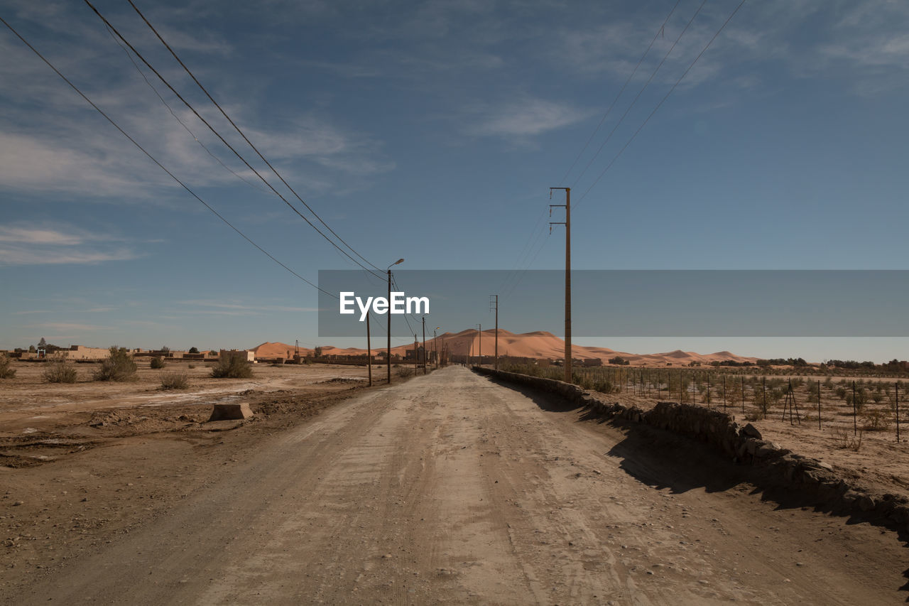 Dirt road and electricity pylons against blue sky