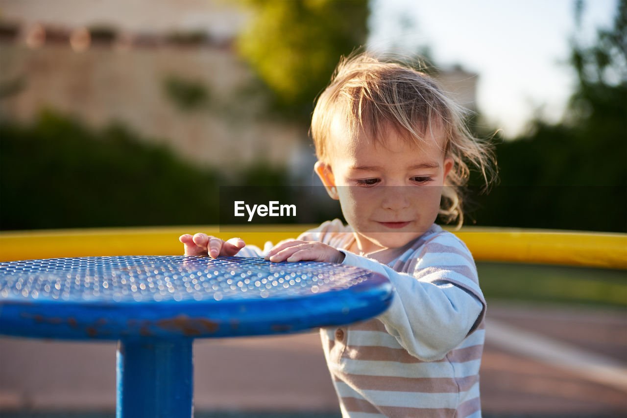 Close-Up Of Boy Holding Play Equipment At Playground