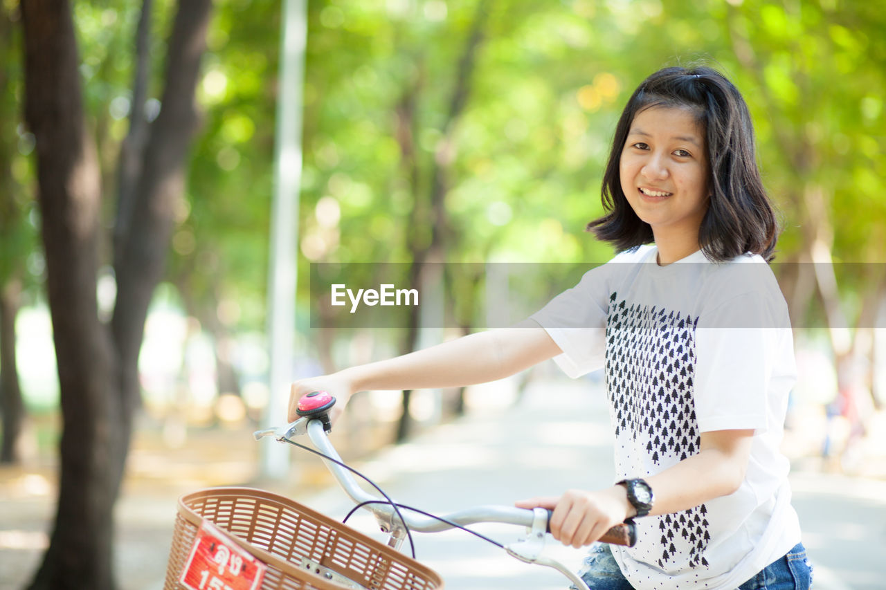 Portrait Of Woman With Bicycle On Road Against Trees
