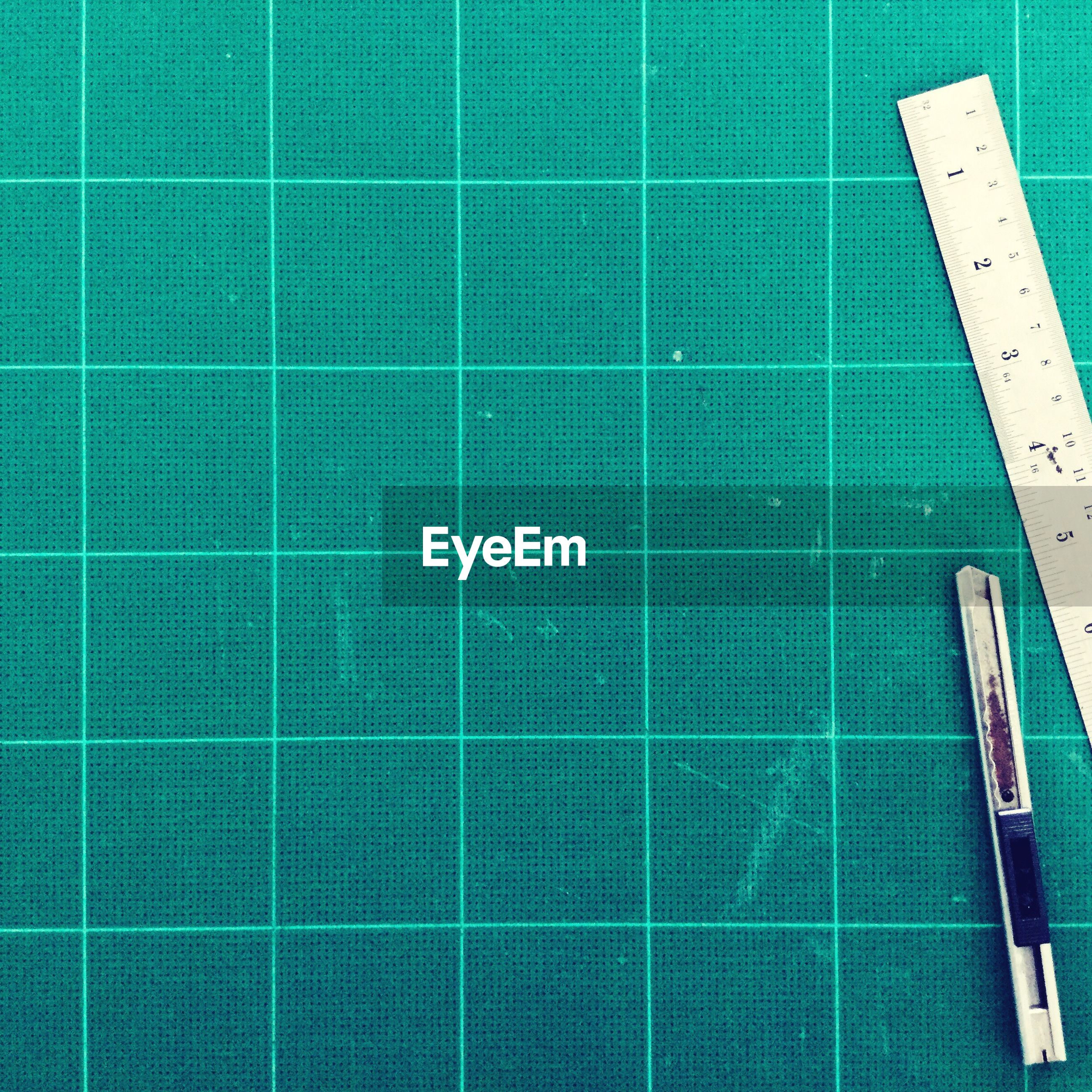 High angle view of ruler on green table