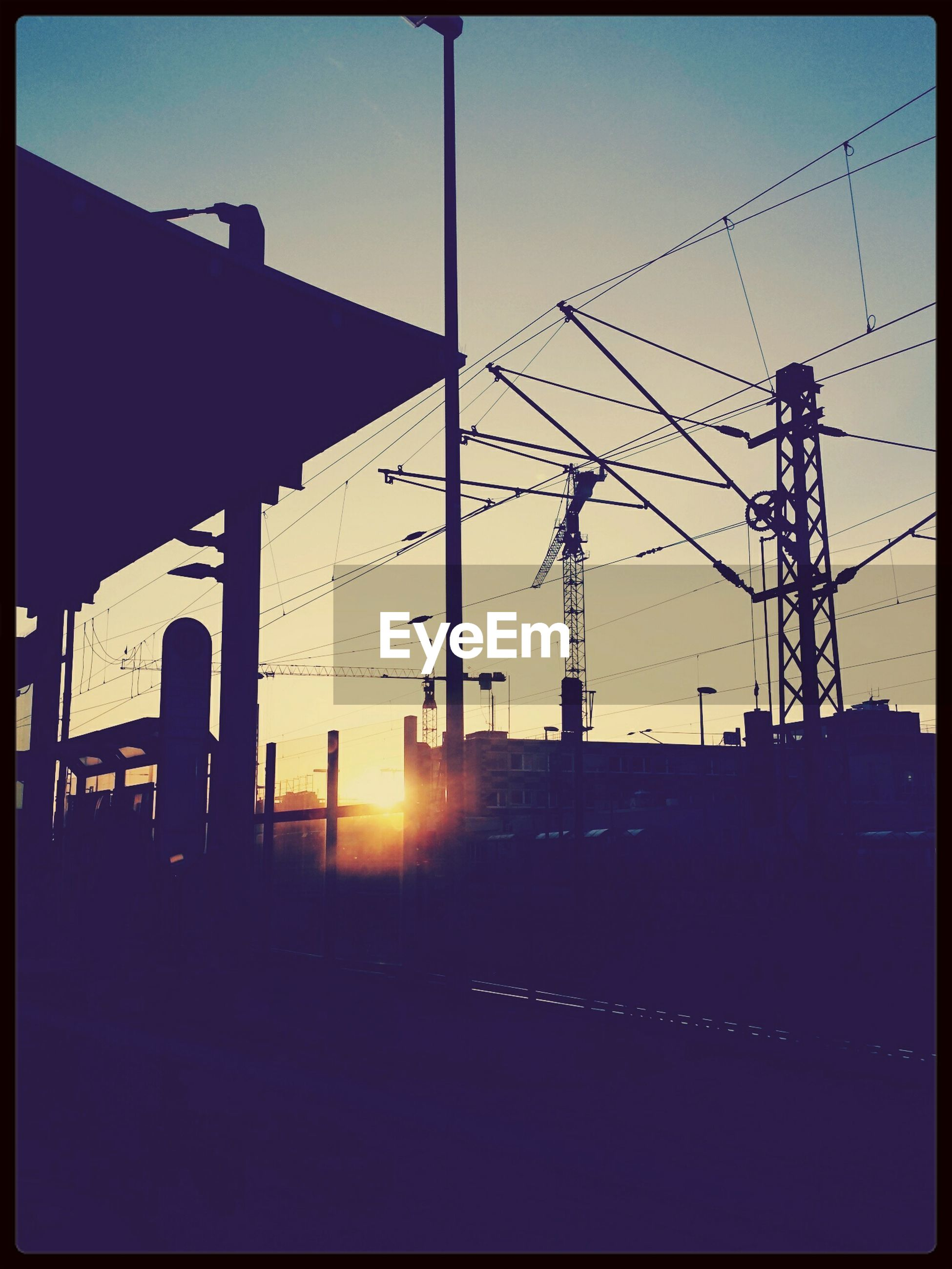 built structure, architecture, silhouette, sunset, power line, sun, building exterior, electricity pylon, transfer print, connection, low angle view, sunlight, sky, electricity, power supply, cable, clear sky, fuel and power generation, auto post production filter, sunbeam