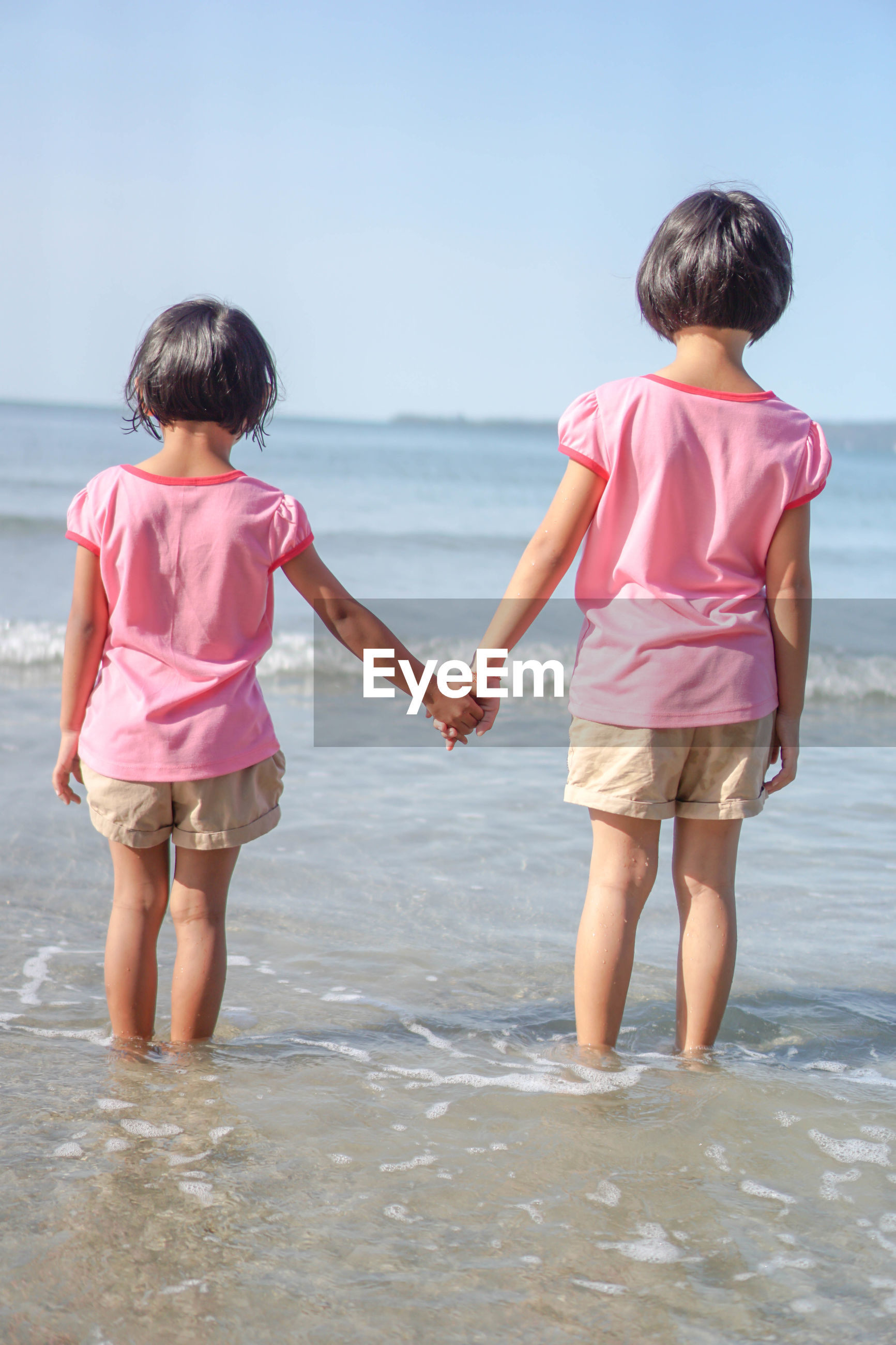 Rear view of sisters holding hands while standing on shore at beach