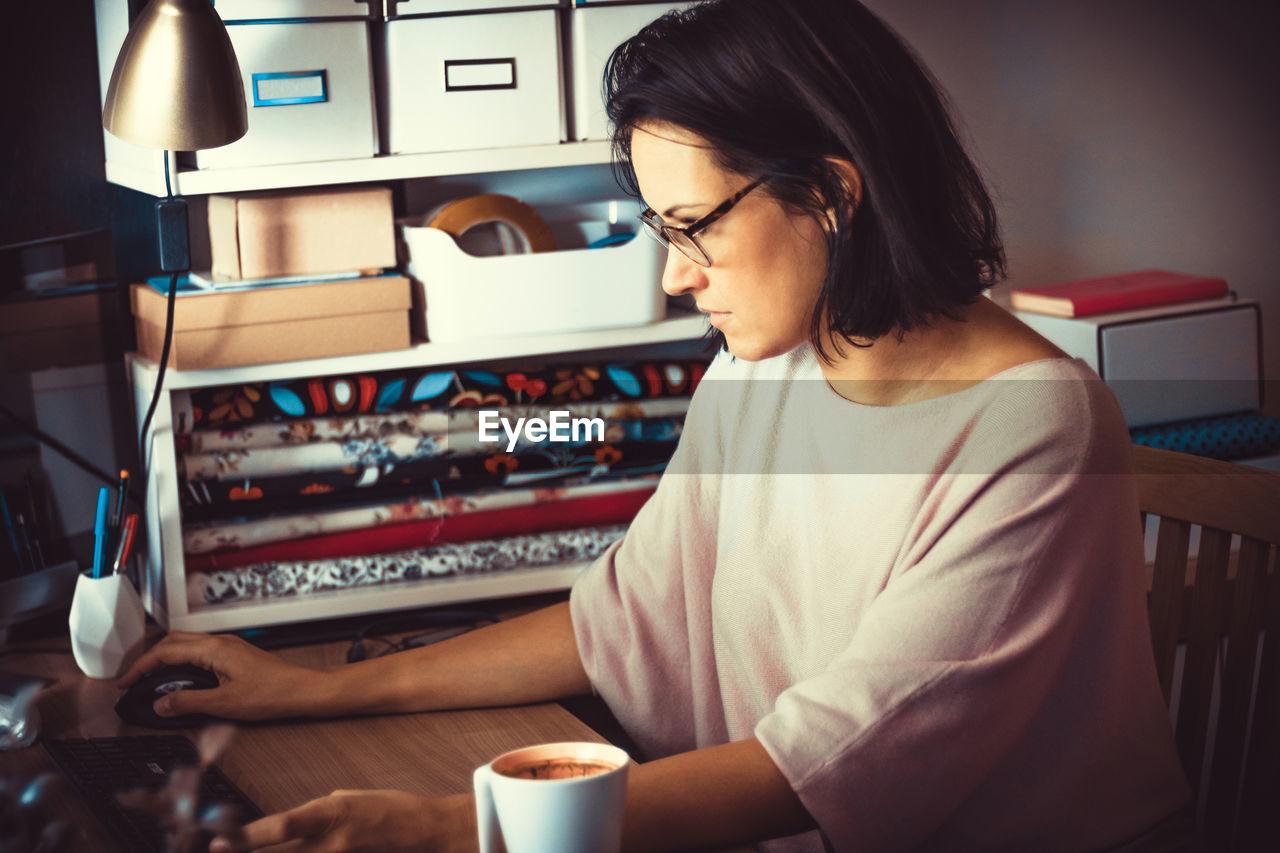 Creative female entrepreneur working on desktop pc at home office.