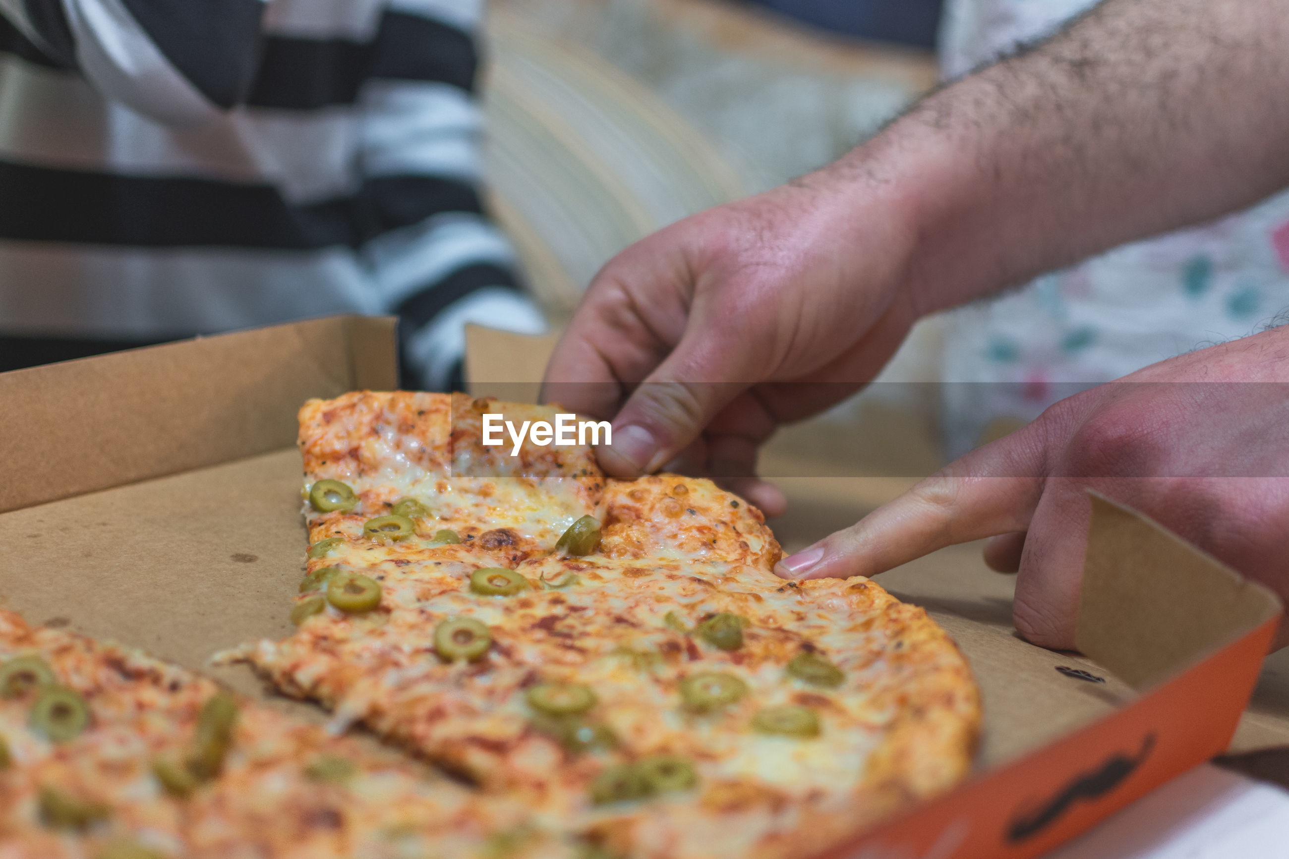 Close-up of hand taking pizza from box