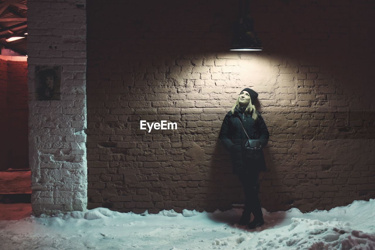 Thoughtful Woman Standing Below Illuminated Pendant Light Against Brick Wall During Winter