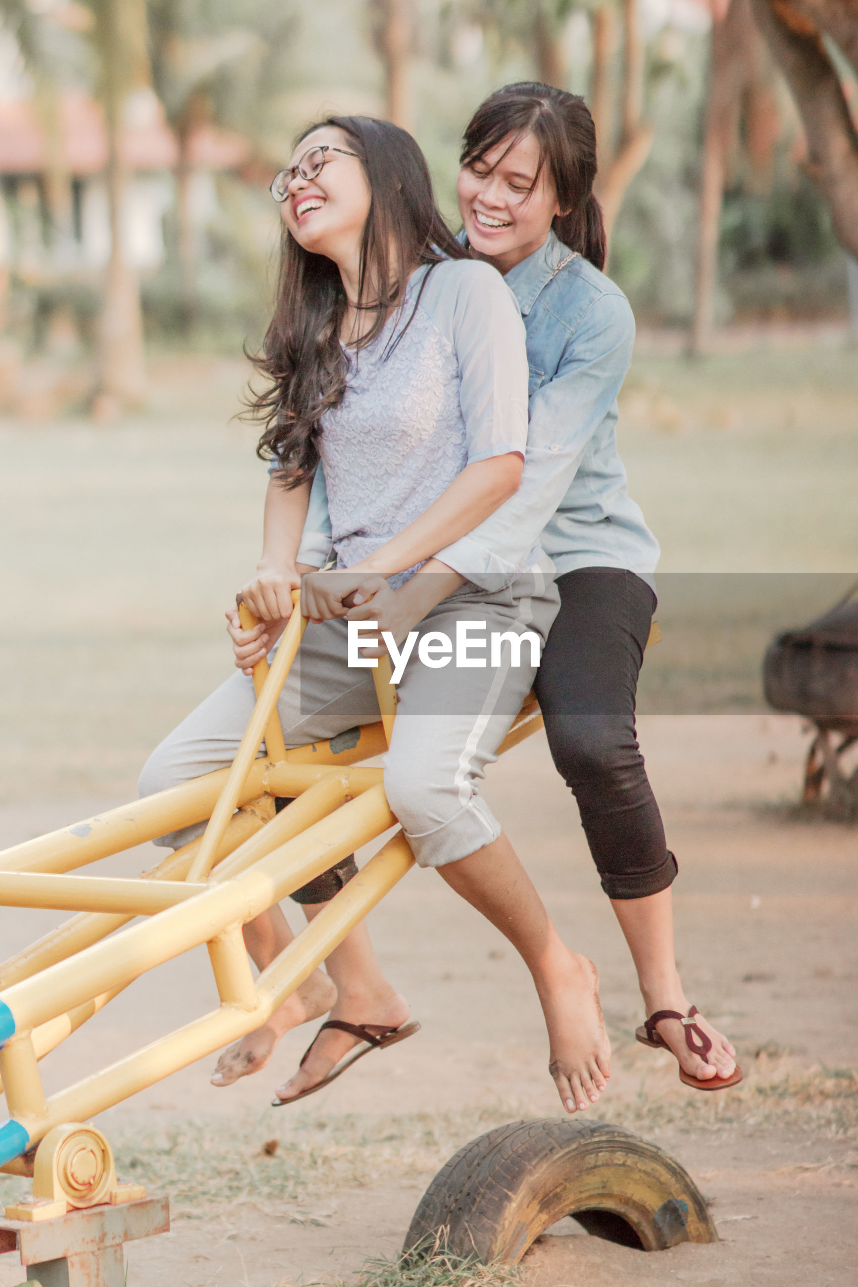 Happy young friends sitting on seesaw