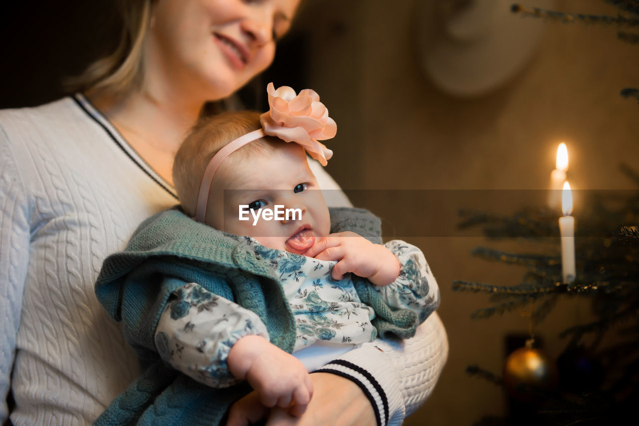 Mother Embracing Cute Baby Girl During Christmas