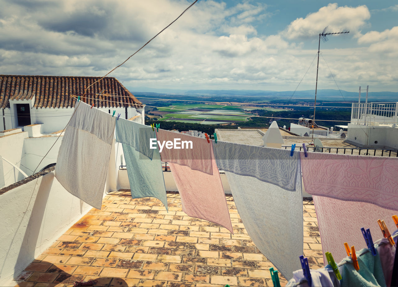 architecture, building exterior, built structure, cloud - sky, sky, hanging, nature, day, city, building, drying, clothesline, no people, outdoors, laundry, sunlight, residential district, water, clothing, town