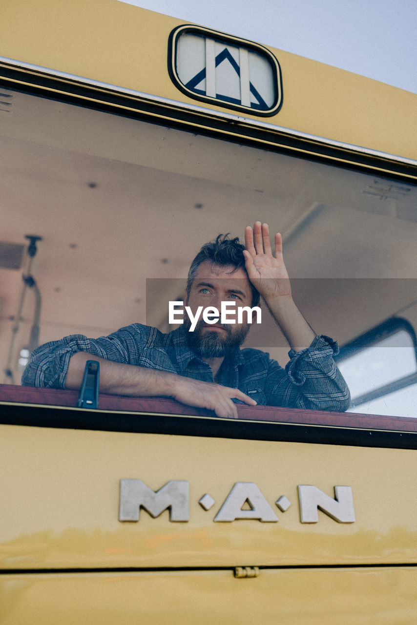 real people, mode of transportation, one person, transportation, land vehicle, communication, front view, car, text, men, portrait, lifestyles, motor vehicle, casual clothing, leisure activity, glass - material, western script, headshot
