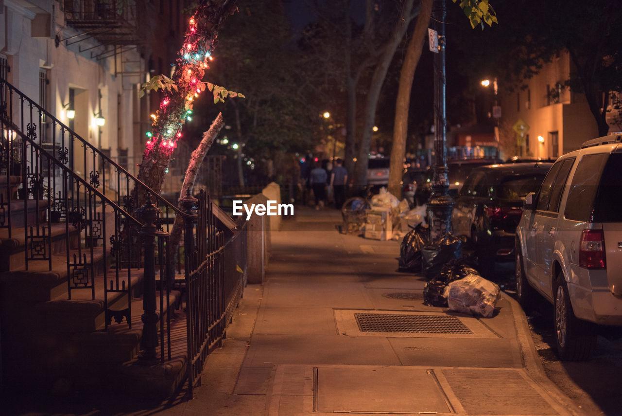 Illuminated footpath by street at night