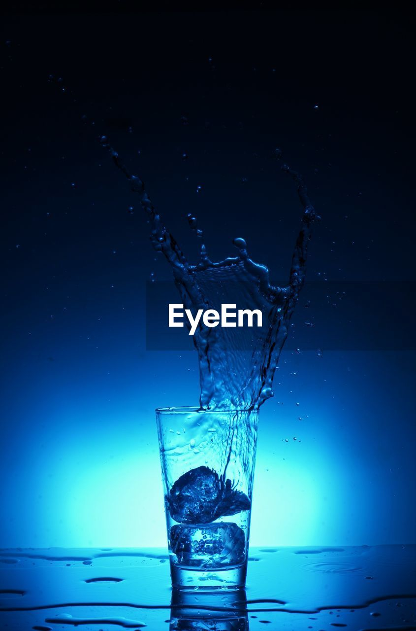 motion, splashing, refreshment, water, drink, drinking glass, blue, no people, food and drink, studio shot, drinking water, freshness, liquid, high-speed photography, purity, close-up, dissolving, splashing droplet, day