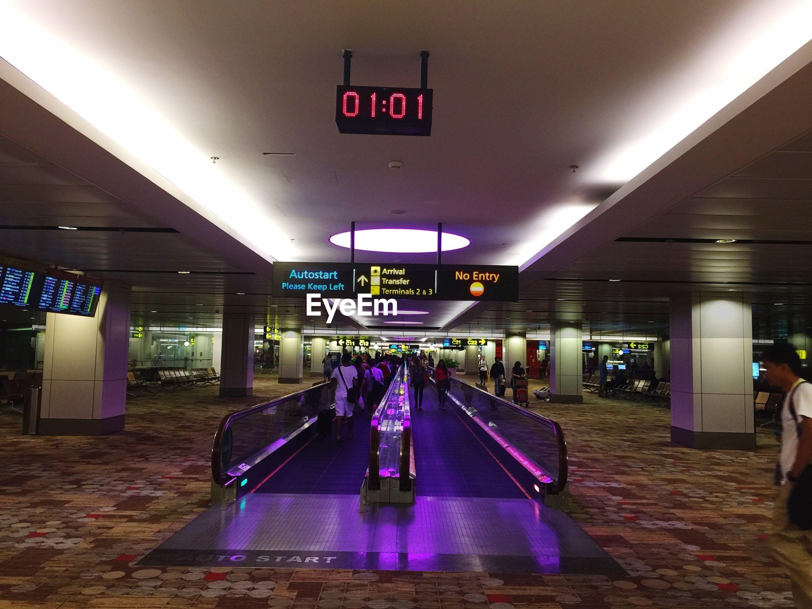 People walking on illuminated escalator at airport