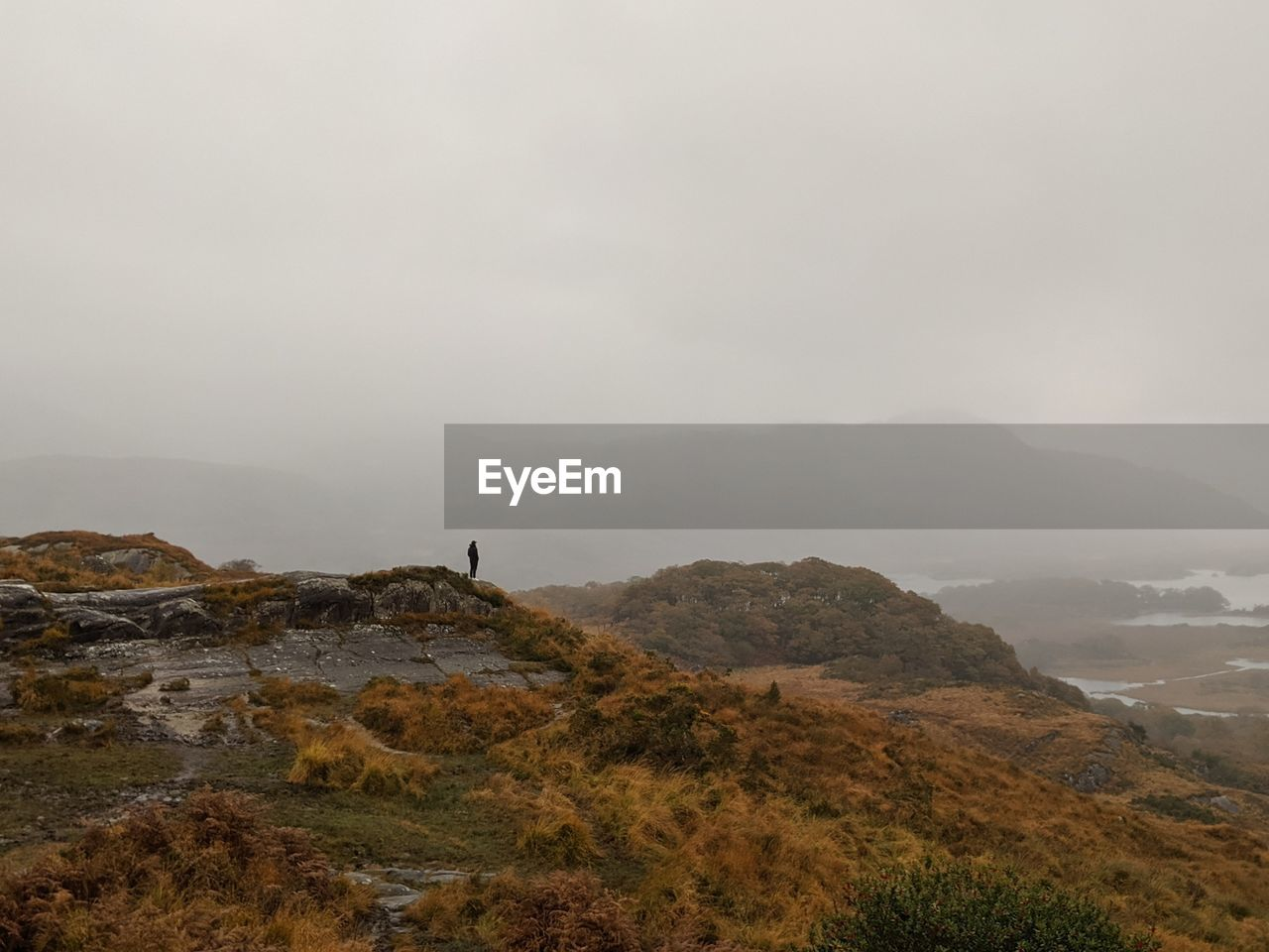 Man standing on mountain against sky in ireland