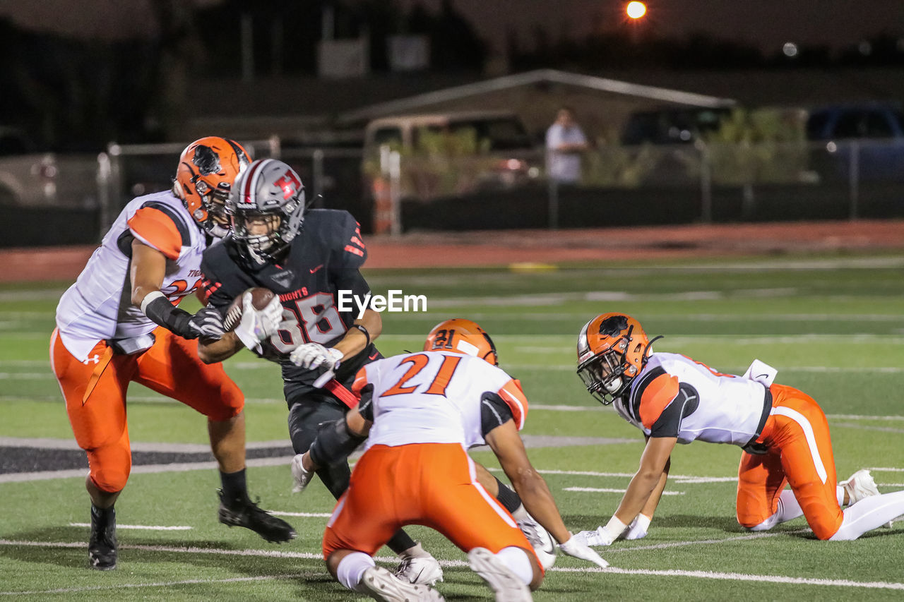 sport, competition, helmet, headwear, playing, sports uniform, american football - sport, sports helmet, american football - ball, sports equipment, clothing, group of people, challenge, security, protection, people, stadium, playing field, running, athlete, teenager