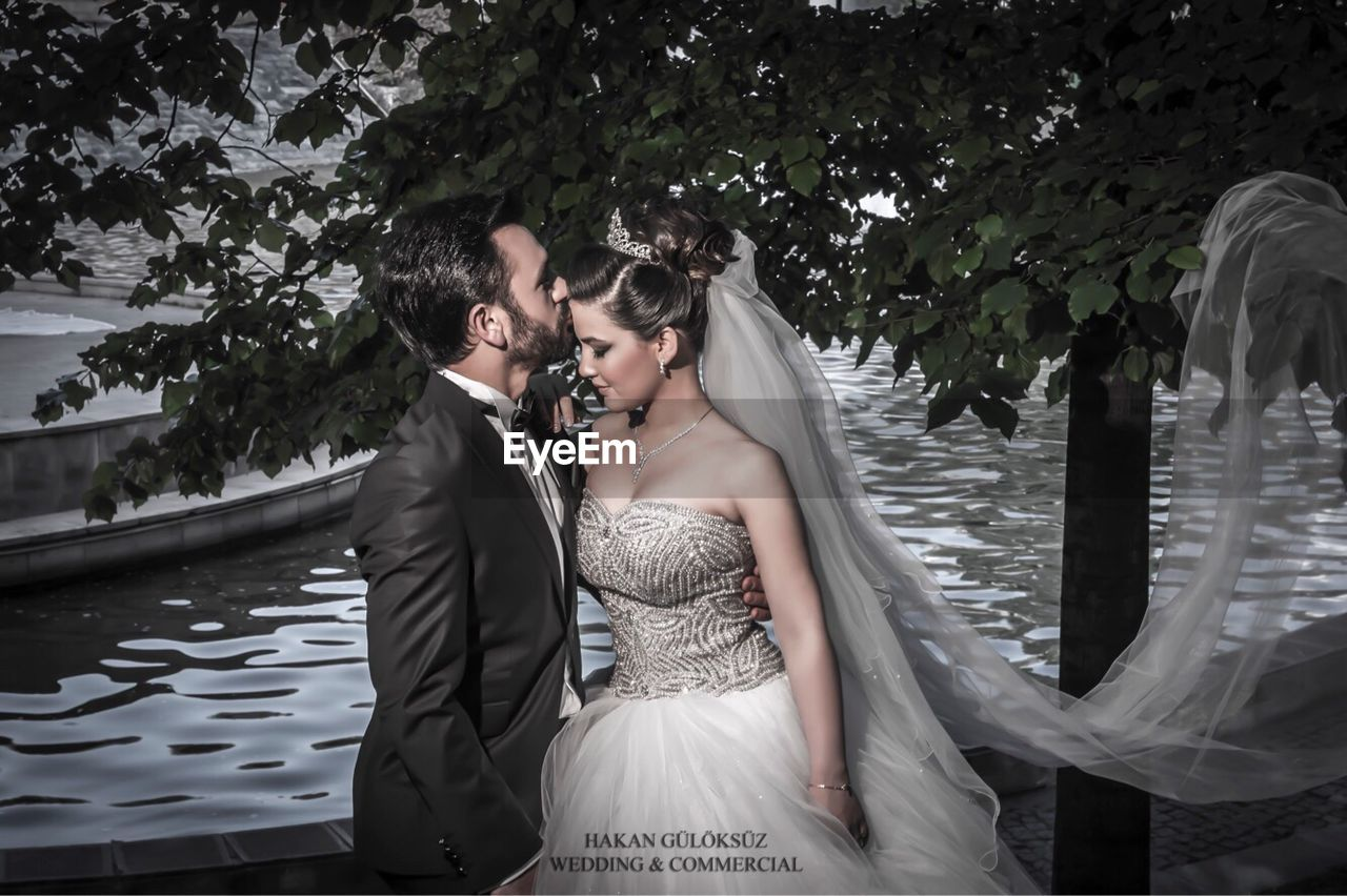 real people, bride, wedding dress, wedding, young women, groom, two people, young adult, well-dressed, togetherness, standing, lifestyles, leisure activity, water, love, outdoors, day, bridegroom, lake, tree