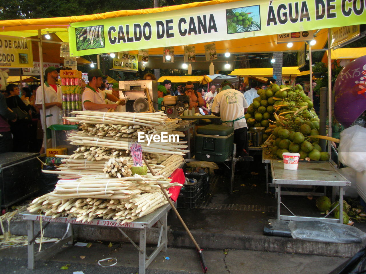 market, retail, group of people, food and drink, real people, healthy eating, food, market stall, crowd, large group of people, business, text, women, for sale, adult, communication, men, choice, vegetable, buying, consumerism, retail display