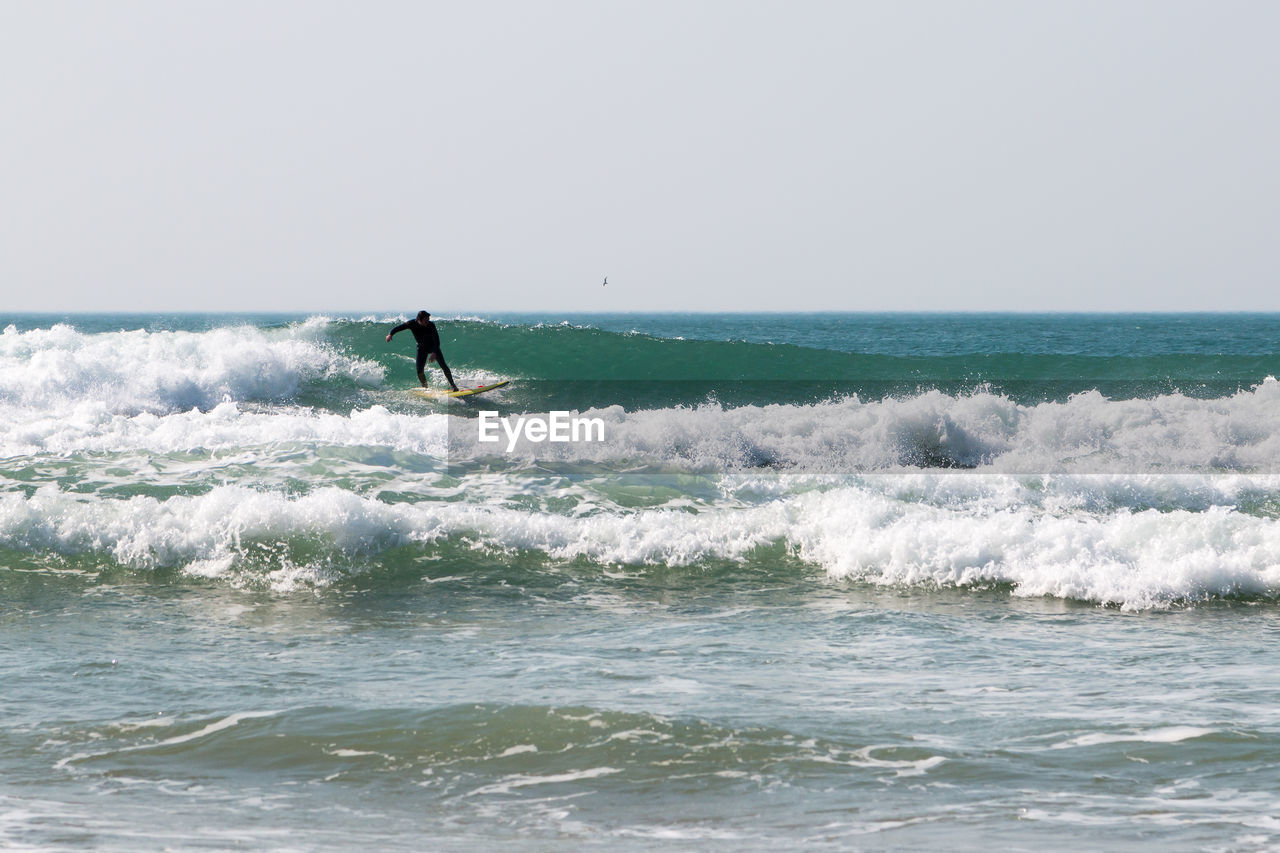 sea, water, wave, horizon over water, motion, sport, one person, sky, waterfront, aquatic sport, surfing, beauty in nature, horizon, real people, lifestyles, leisure activity, adventure, men, extreme sports, skill, outdoors, power in nature