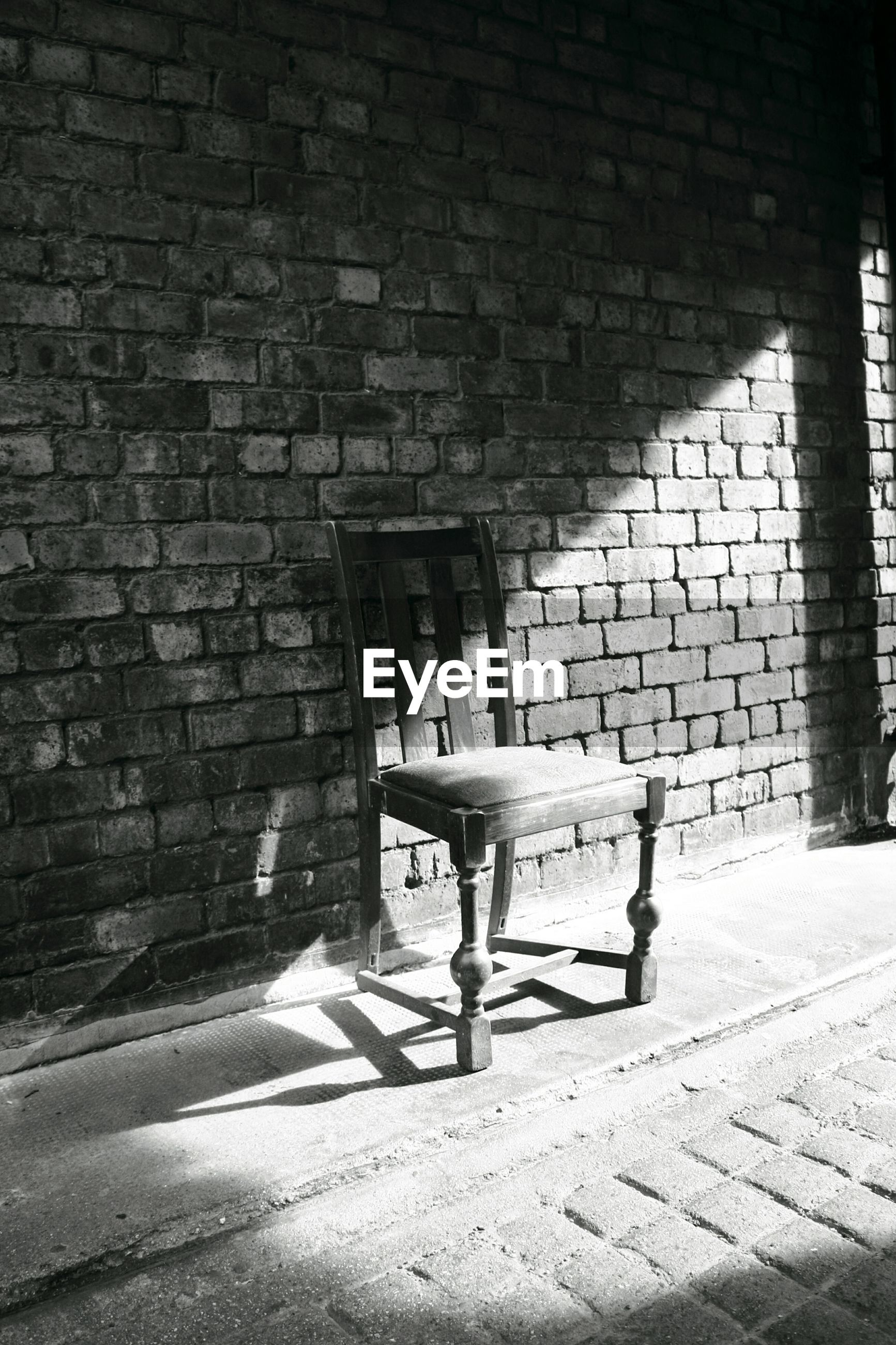 Empty abandoned chair in sunlight against brick wall