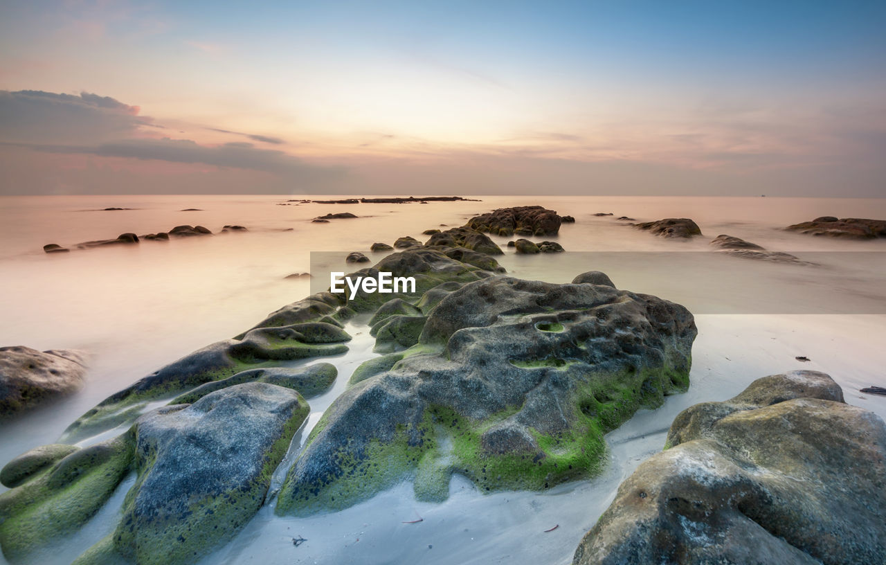 sunset, sea, nature, beauty in nature, sky, scenics, tranquil scene, tranquility, water, rock - object, no people, outdoors, beach, horizon over water, day