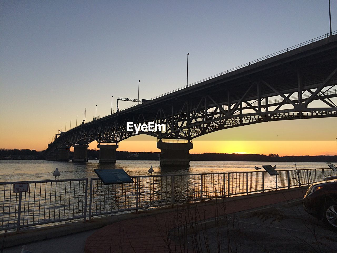 water, sky, bridge, built structure, architecture, connection, bridge - man made structure, sunset, transportation, nature, engineering, river, clear sky, orange color, outdoors, mode of transportation, travel destinations, bay, long