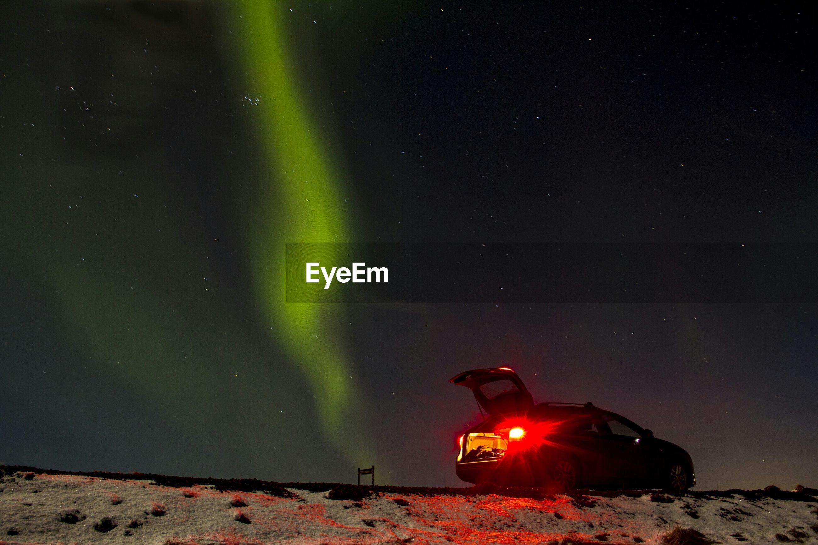 Illuminated car on snow covered field against aurora borealis