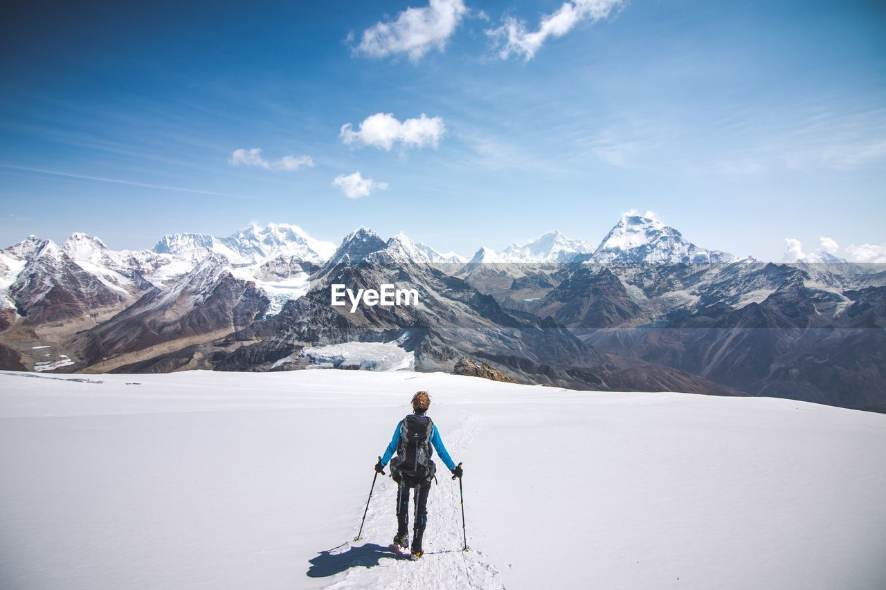 Rear View Of Man Hiking On Snow Covered Field By Mountains Against Sky