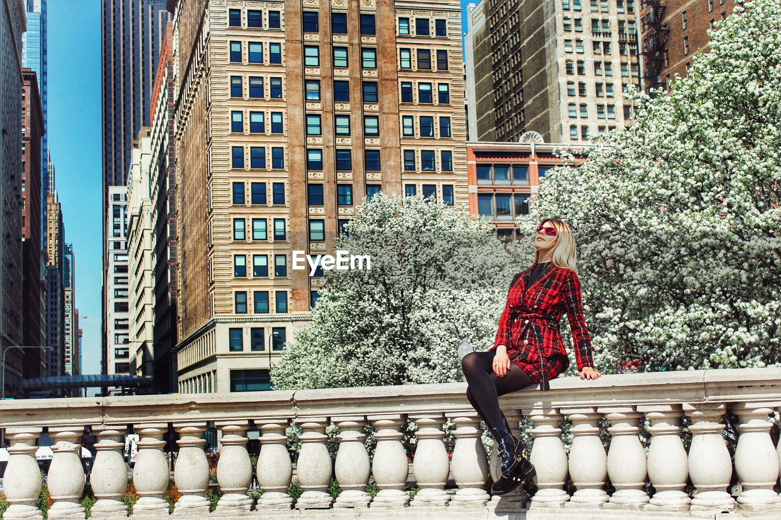 Fashionable woman sitting on retaining wall in city