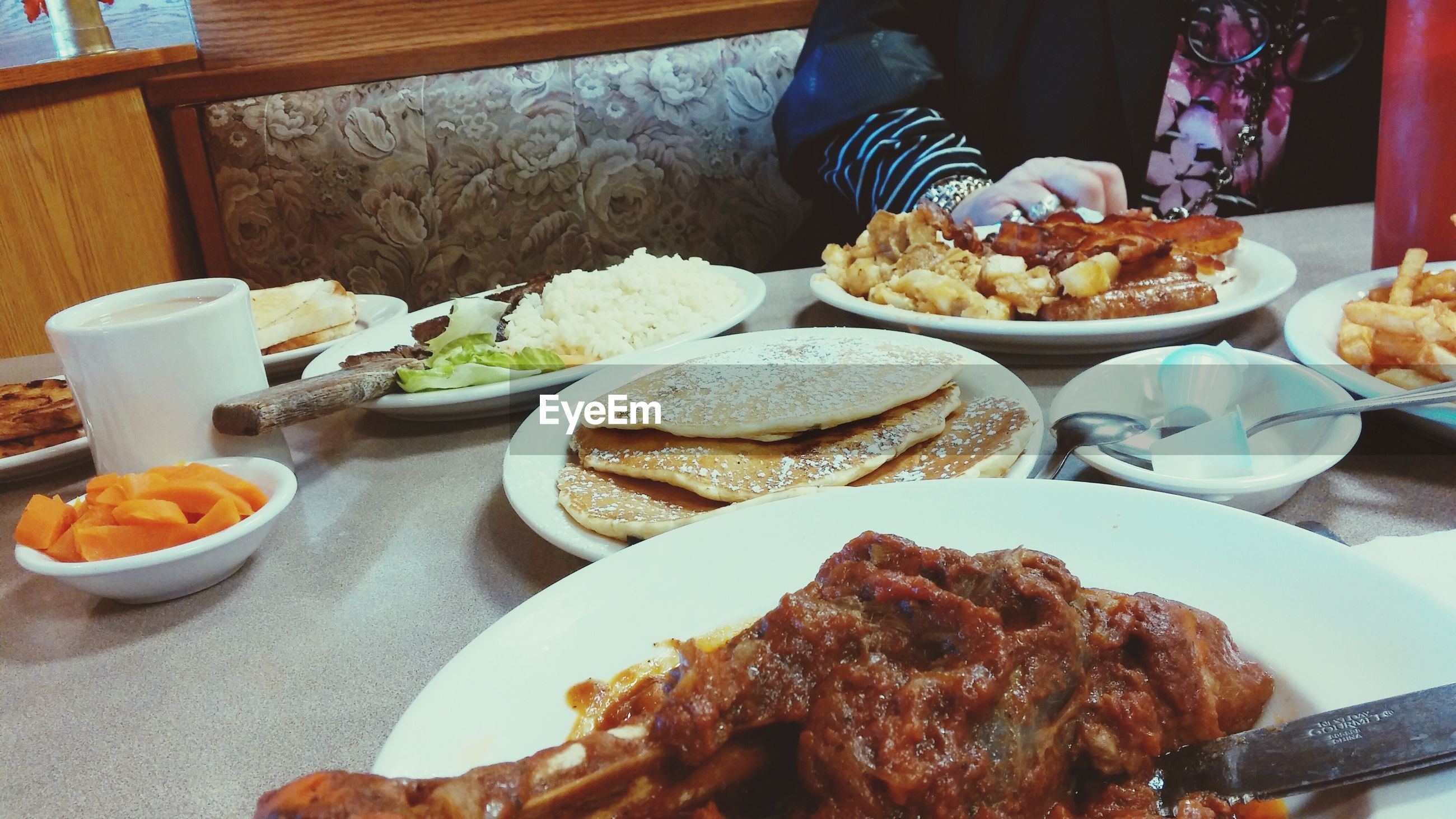 Midsection of woman having food at table