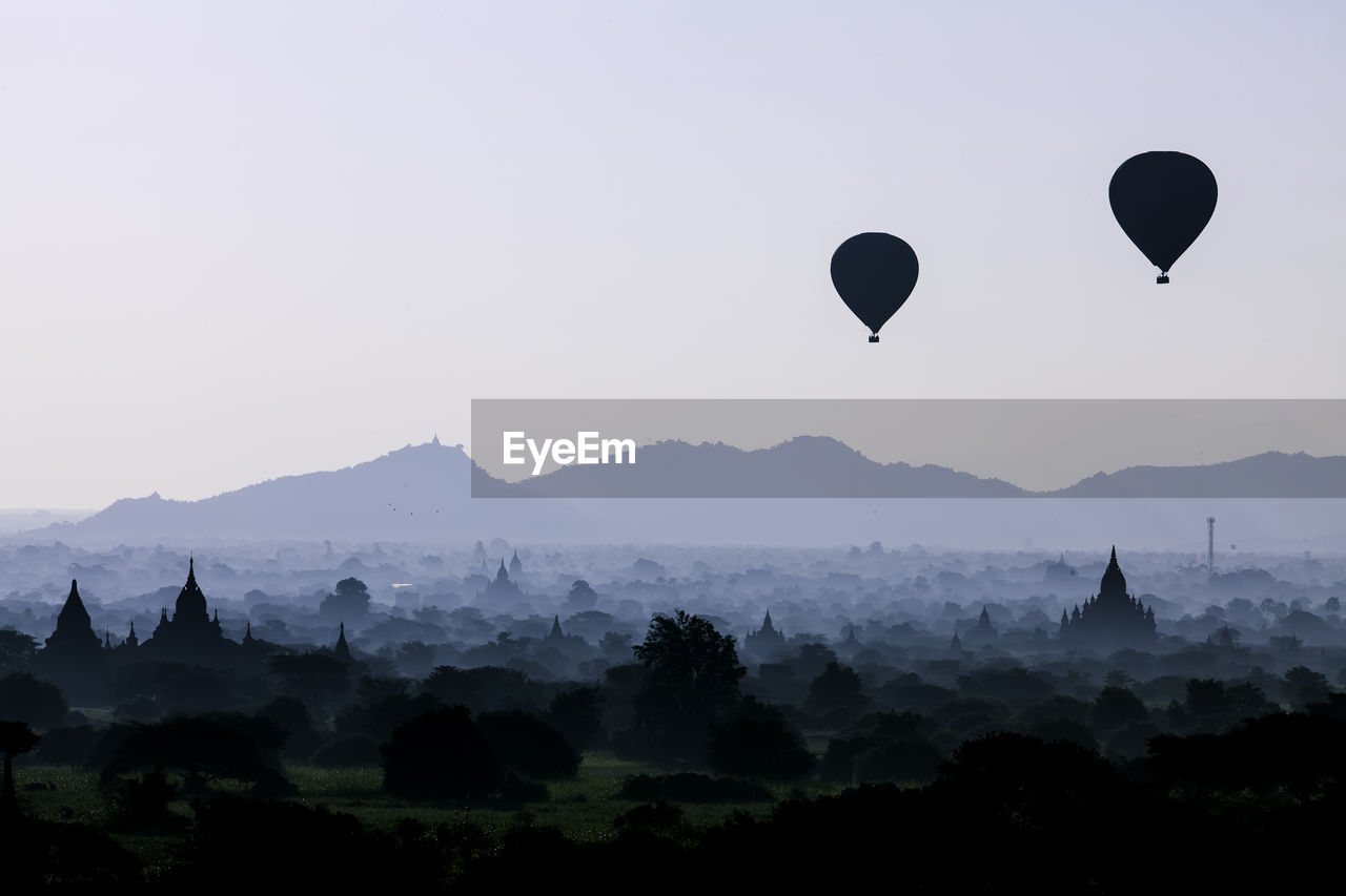 hot air balloon, air vehicle, sky, balloon, scenics - nature, tree, mountain, flying, mid-air, travel destinations, nature, travel, plant, transportation, beauty in nature, place of worship, belief, architecture, mode of transportation, silhouette, no people