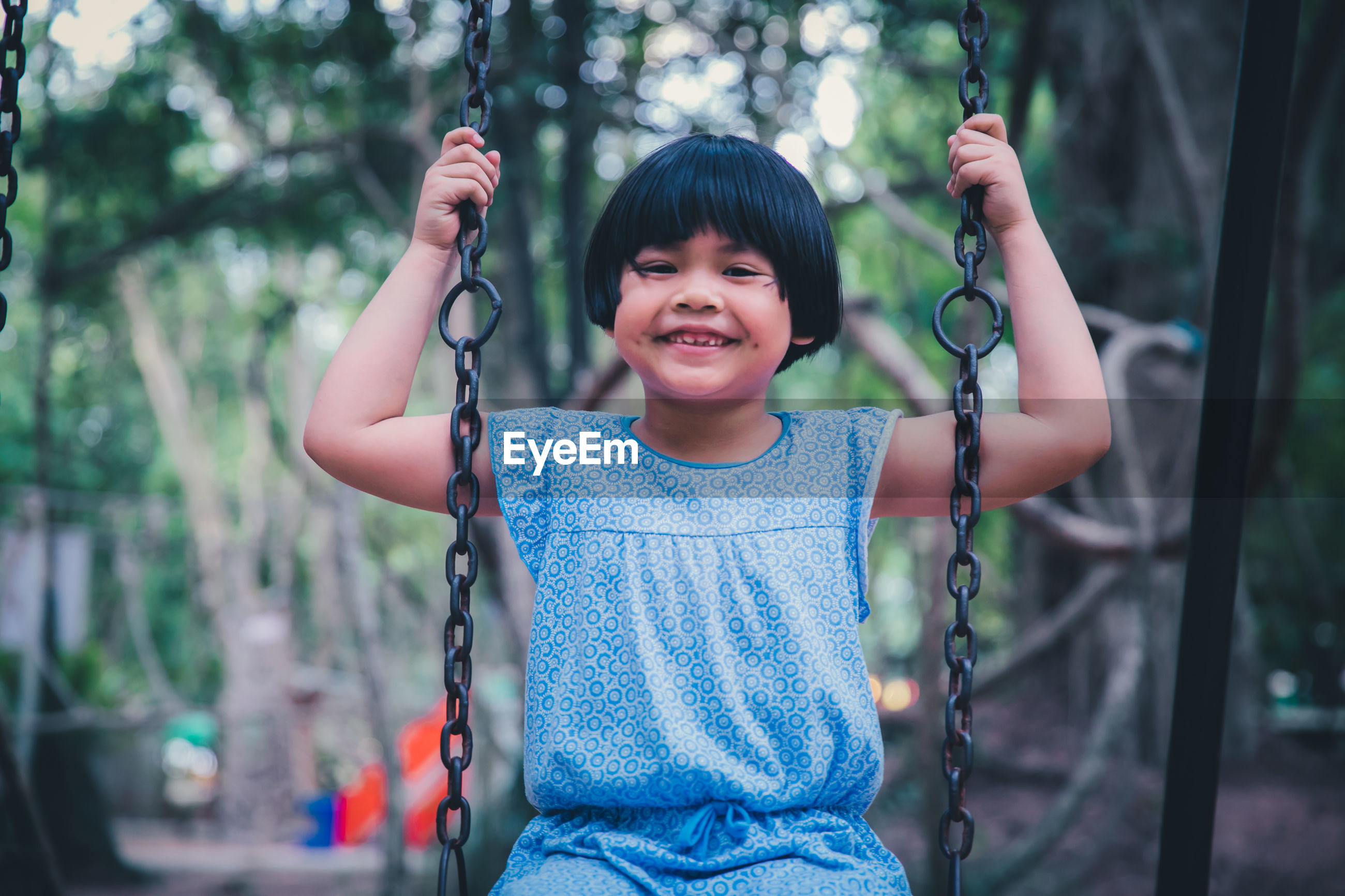 Portrait of smiling girl swinging at playground