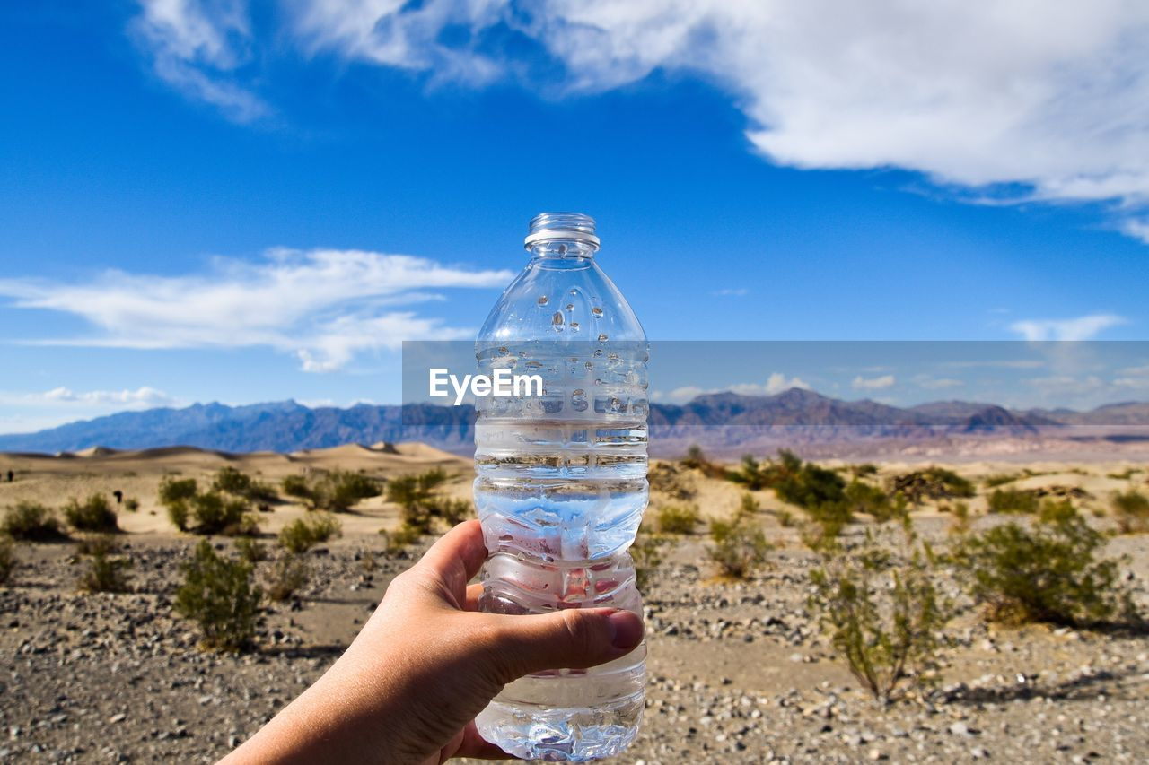 Cropped Hand Of Person Holding Water Bottle In Desert Against Sky