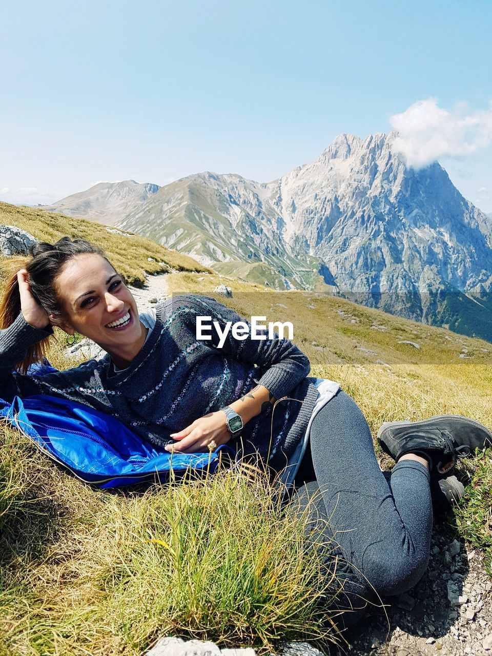 Portrait of smiling woman lying at mountain against sky