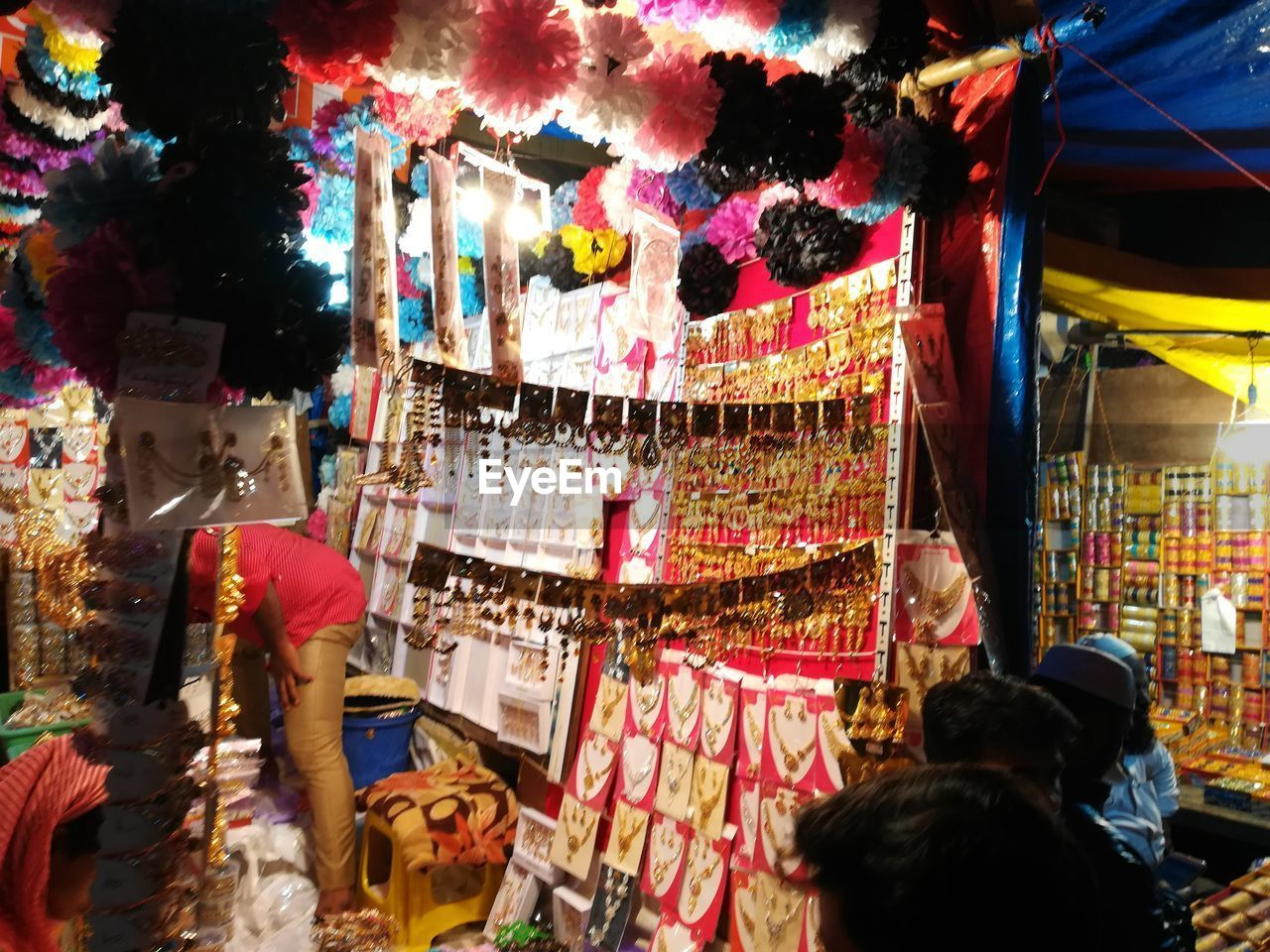 retail, market, for sale, choice, market stall, variation, real people, multi colored, hanging, night, illuminated, group of people, business, large group of objects, small business, city, decoration, women, collection, shopping, sale, buying, outdoors, retail display, consumerism, street market