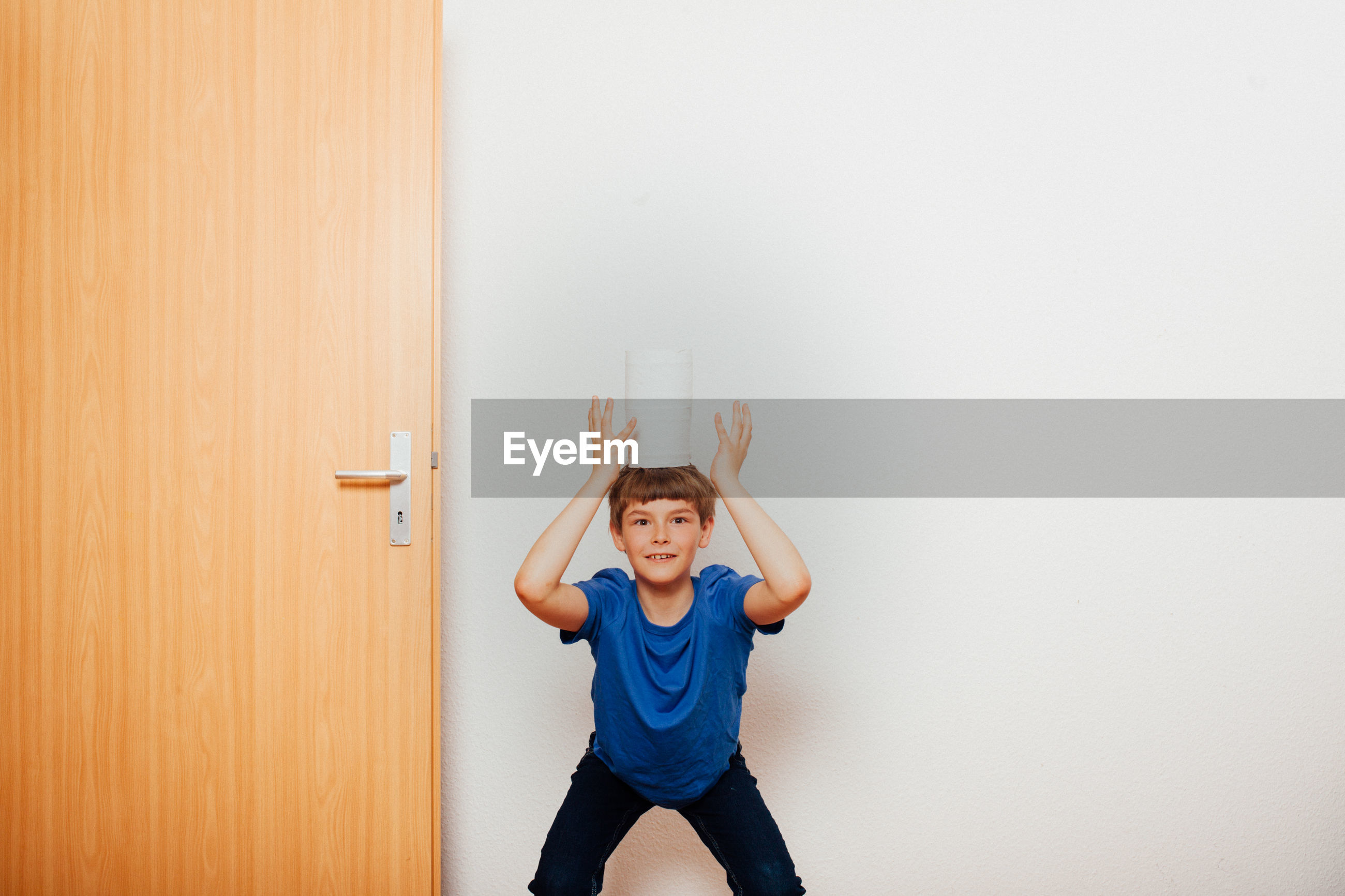 Boy with tissue roles standing by door