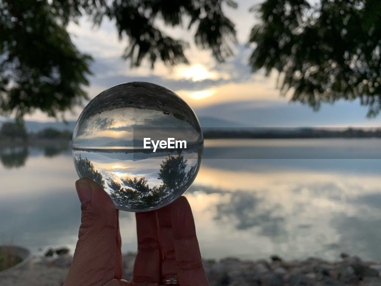 one person, water, reflection, sphere, holding, crystal ball, human hand, hand, focus on foreground, nature, sky, human body part, transparent, beauty in nature, unrecognizable person, real people, scenics - nature, lake, cloud - sky, outdoors, finger