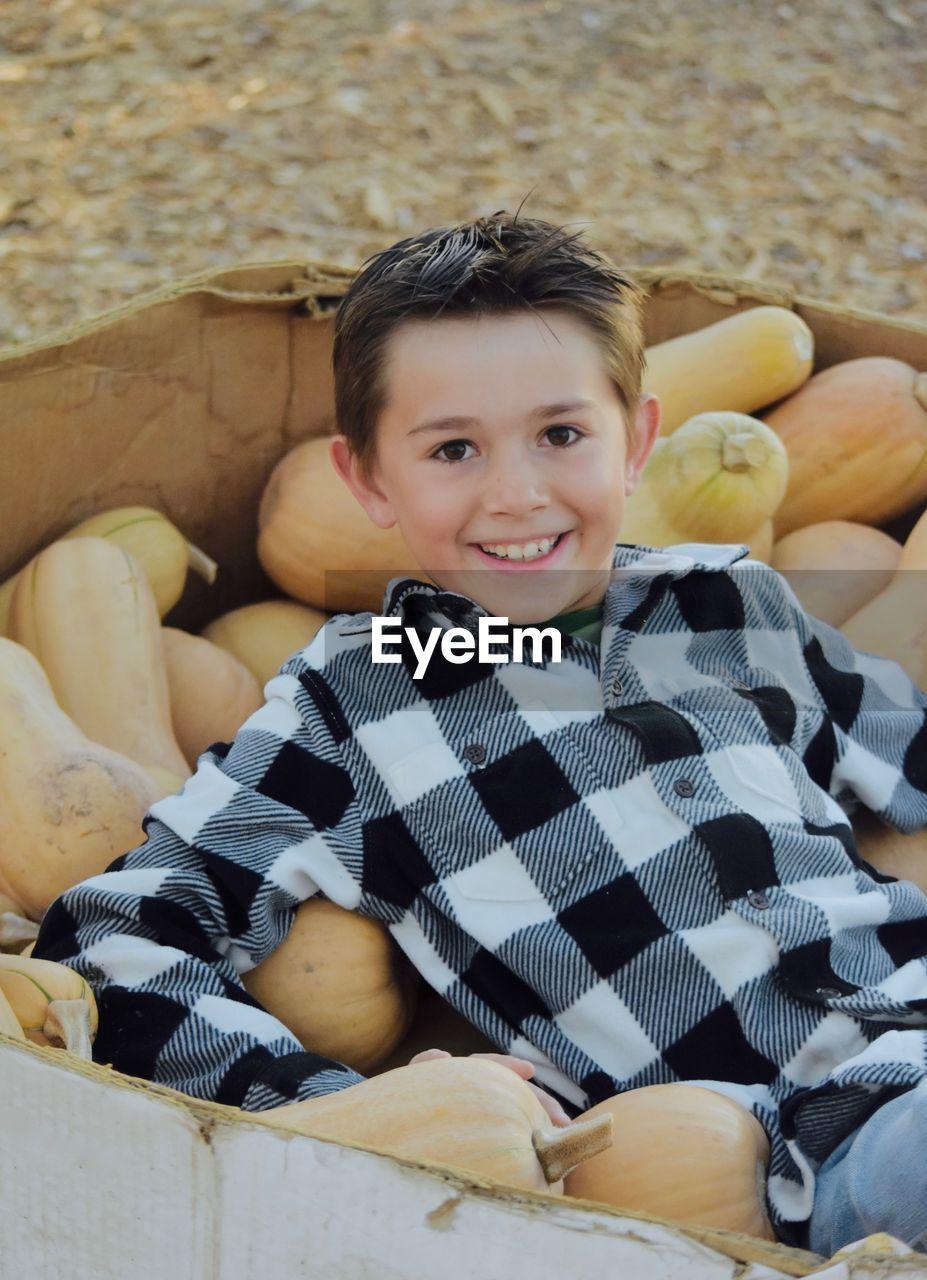 Portrait Of Happy Boy Sitting In Box With Pumpkins