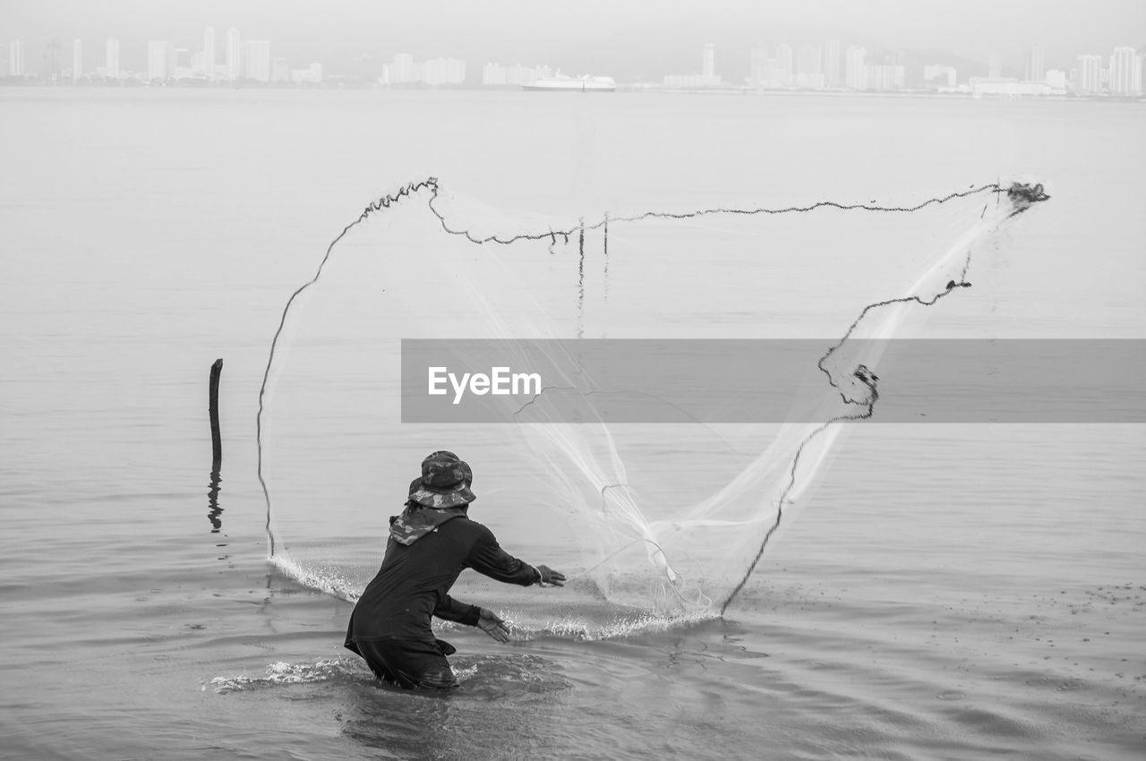 Man throwing fishing net in sea