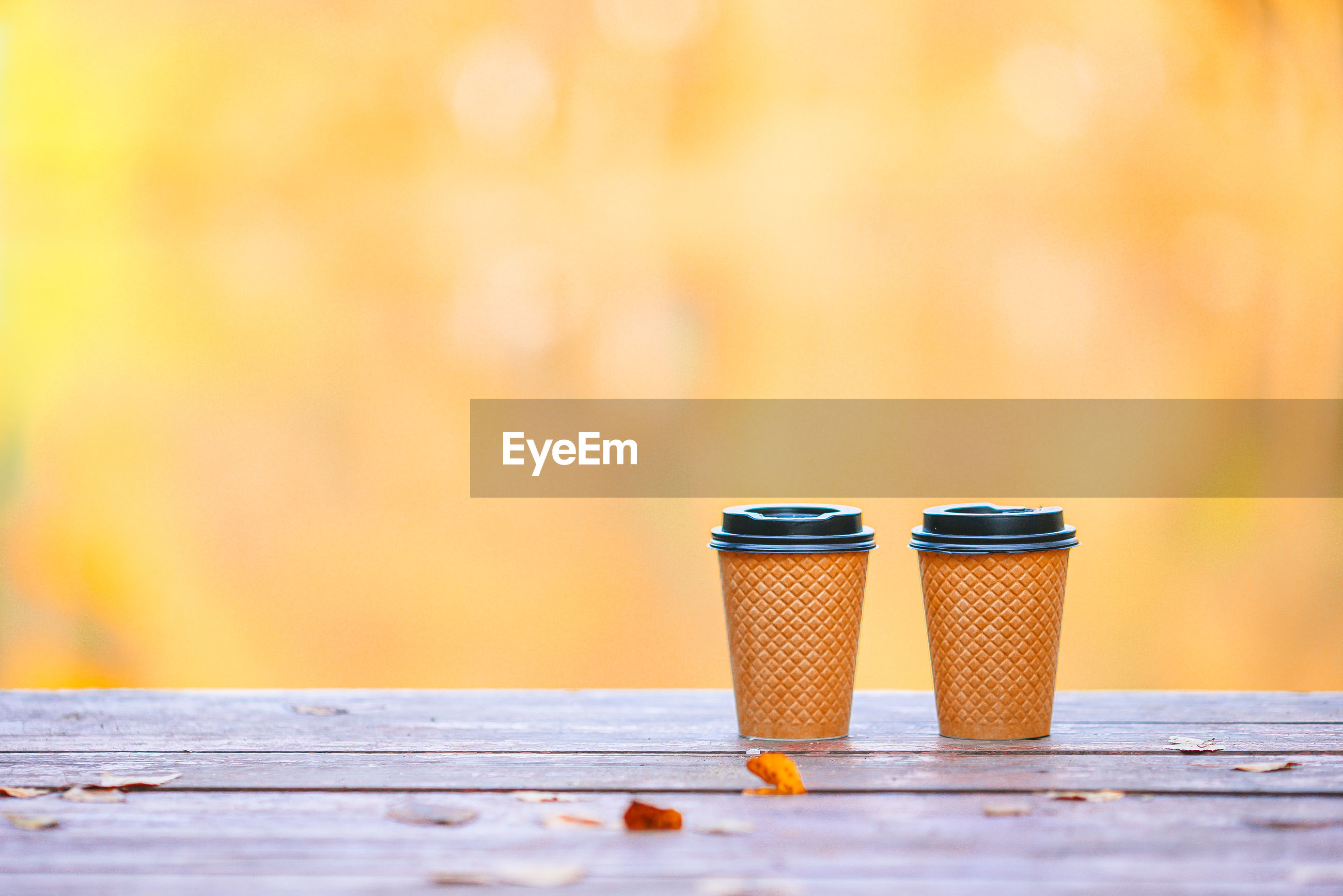 CLOSE-UP OF COFFEE ON TABLE AGAINST ORANGE WALL
