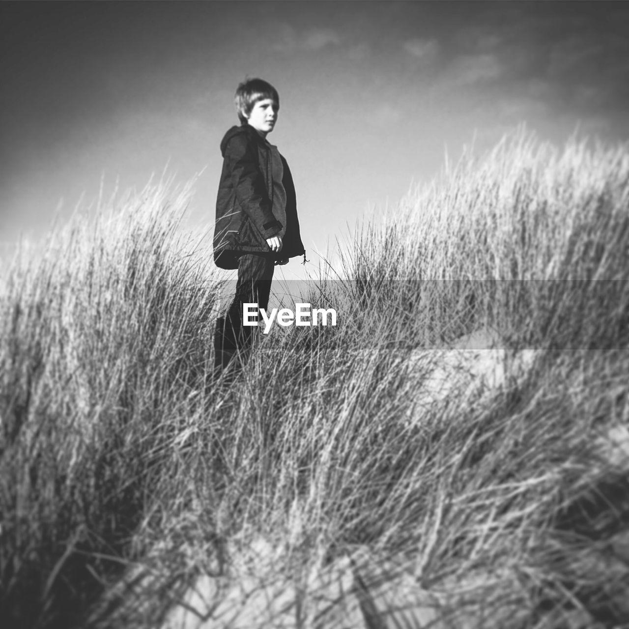 Boy Standing On Grassy Field Against Sky