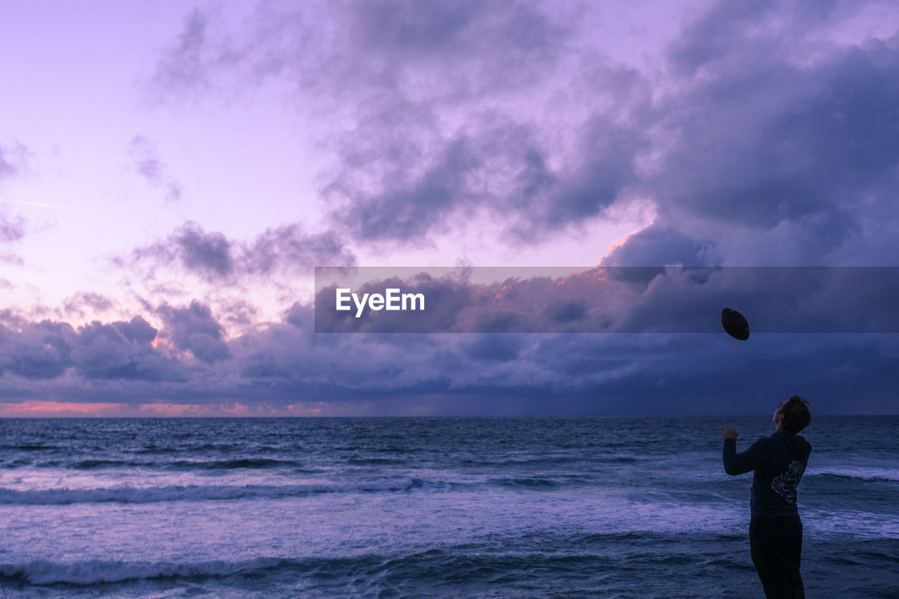 sky, sea, cloud - sky, real people, sunset, one person, water, leisure activity, ball, beach, beauty in nature, lifestyles, horizon over water, horizon, nature, land, playing, motion, outdoors, purple