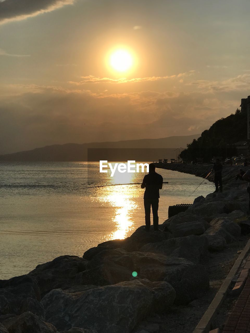 sky, sunset, water, sea, beauty in nature, sun, real people, rock, scenics - nature, rock - object, standing, leisure activity, lifestyles, solid, one person, nature, beach, full length, horizon over water, outdoors
