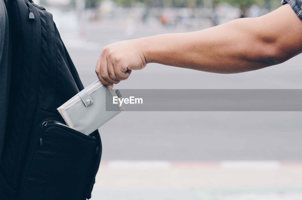 human hand, focus on foreground, hand, holding, real people, human body part, midsection, one person, lifestyles, day, bag, selective focus, outdoors, business, leisure activity, standing, close-up, finance, city, consumerism, finger