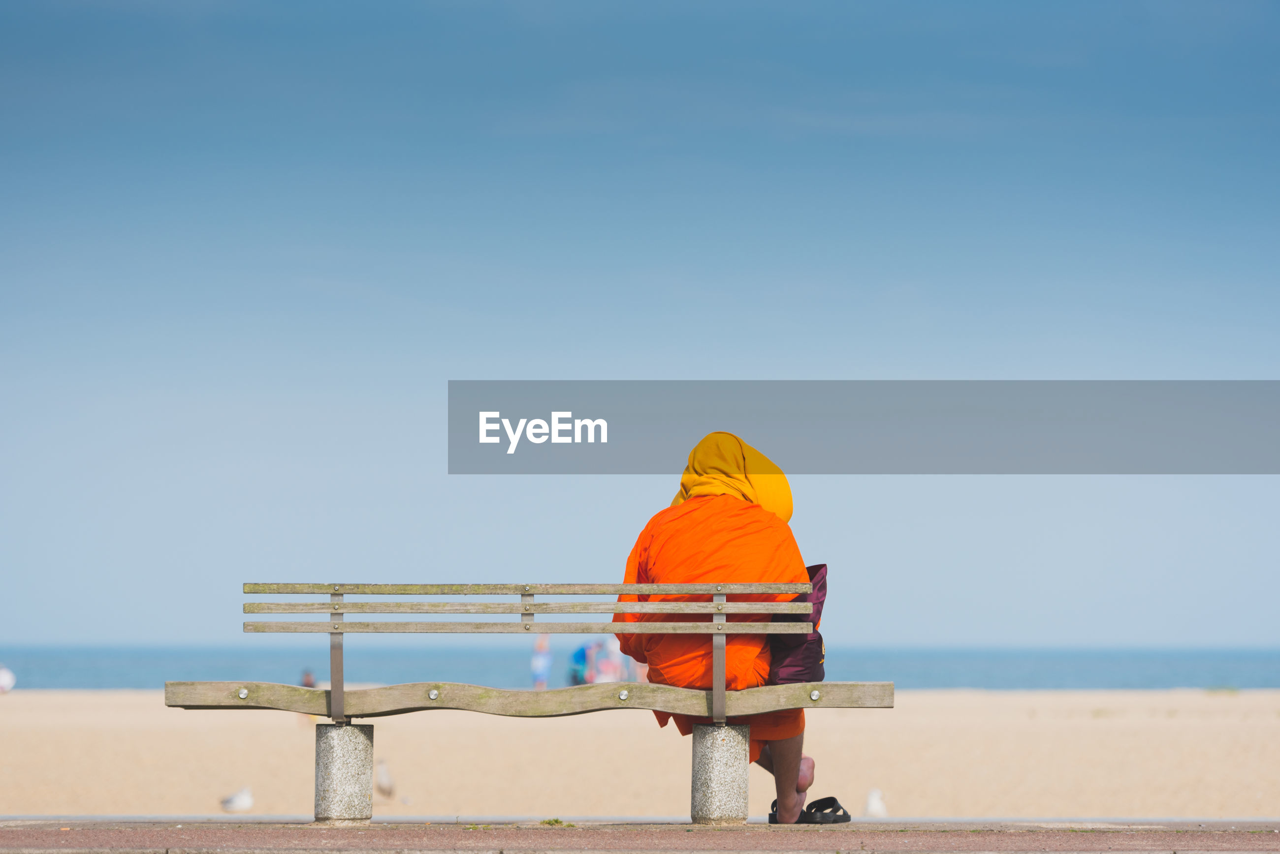Rear view of monk sitting on bench at beach against sky