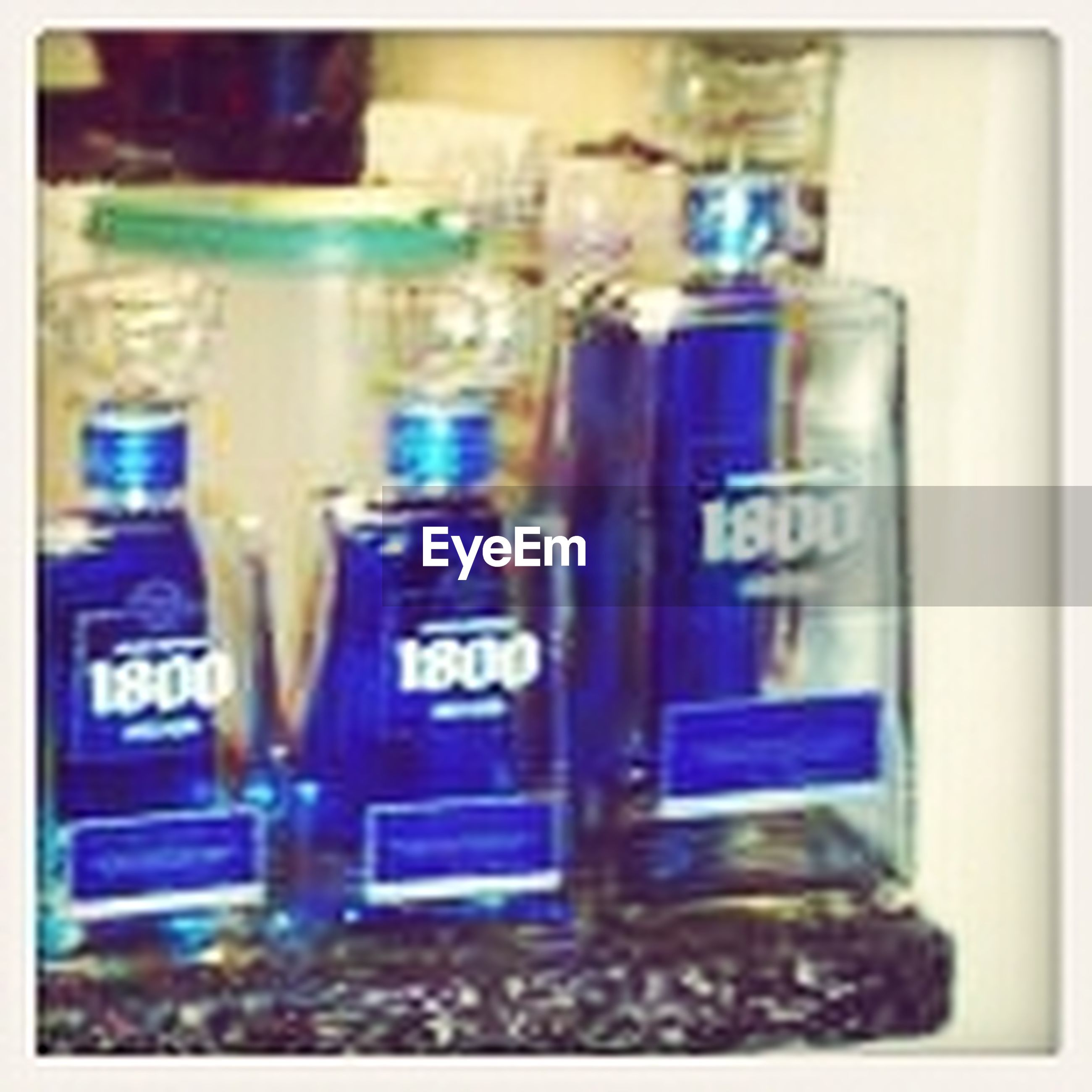 indoors, transfer print, communication, selective focus, auto post production filter, focus on foreground, text, close-up, western script, blue, variation, glass - material, no people, transparent, technology, still life, bottle, in a row, large group of objects, reflection