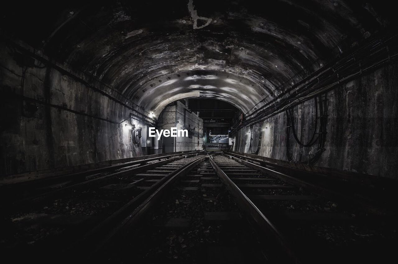 architecture, rail transportation, railroad track, track, transportation, the way forward, tunnel, arch, diminishing perspective, direction, built structure, indoors, public transportation, illuminated, vanishing point, no people, light at the end of the tunnel, lighting equipment, mode of transportation, ceiling, long