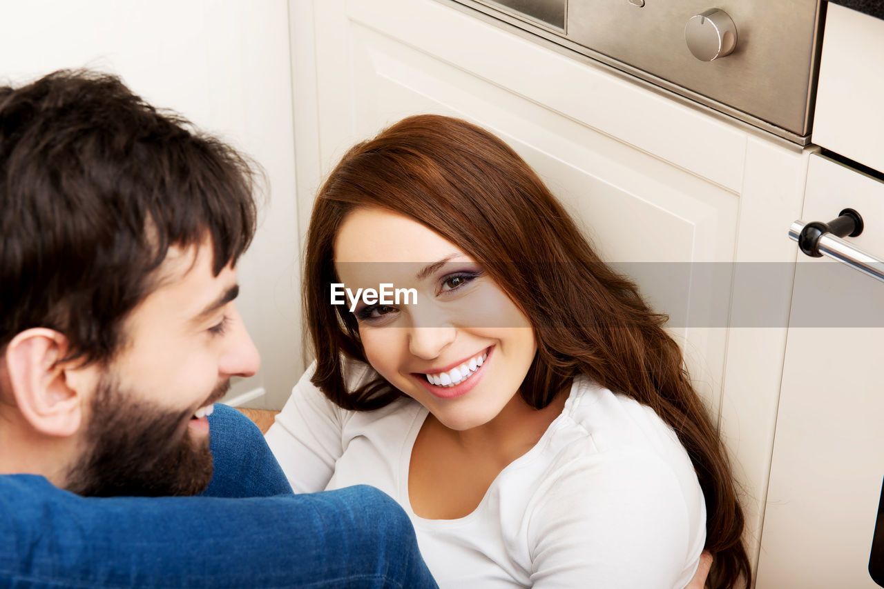 Close-up of smiling couple sitting at home