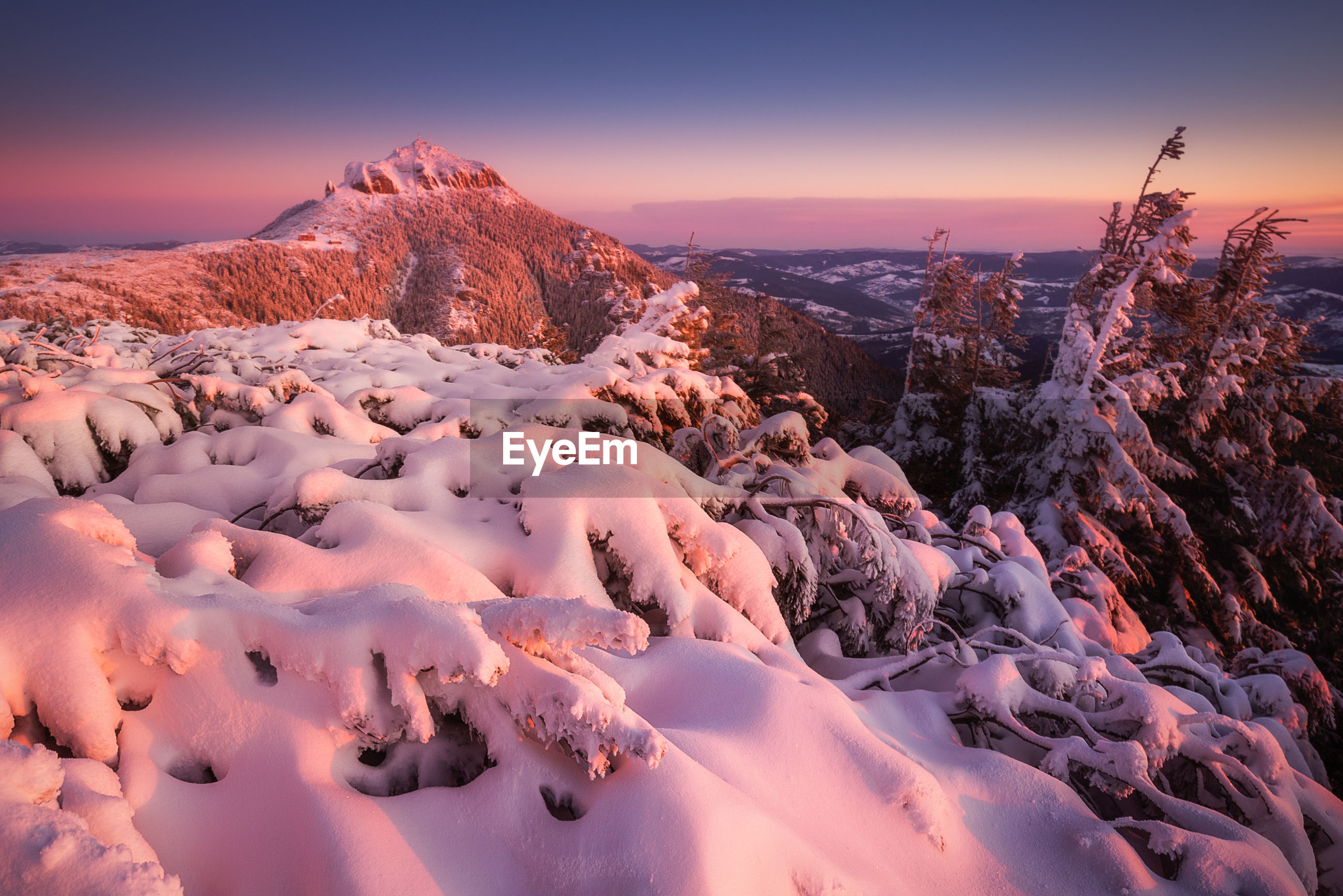 Scenic view of snow mountains against sky during sunset in ceahlau mountains