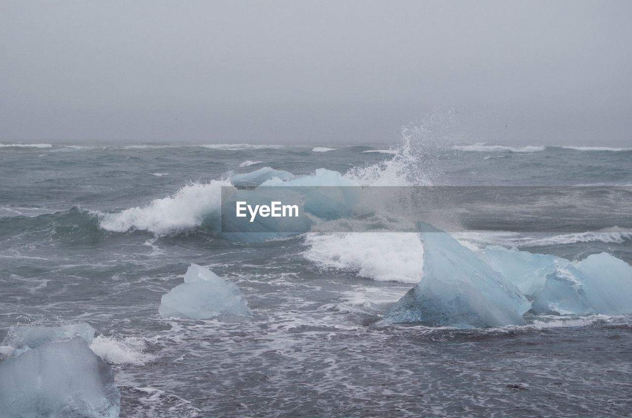 Scenic View Of Sea With Icebergs Against Sky